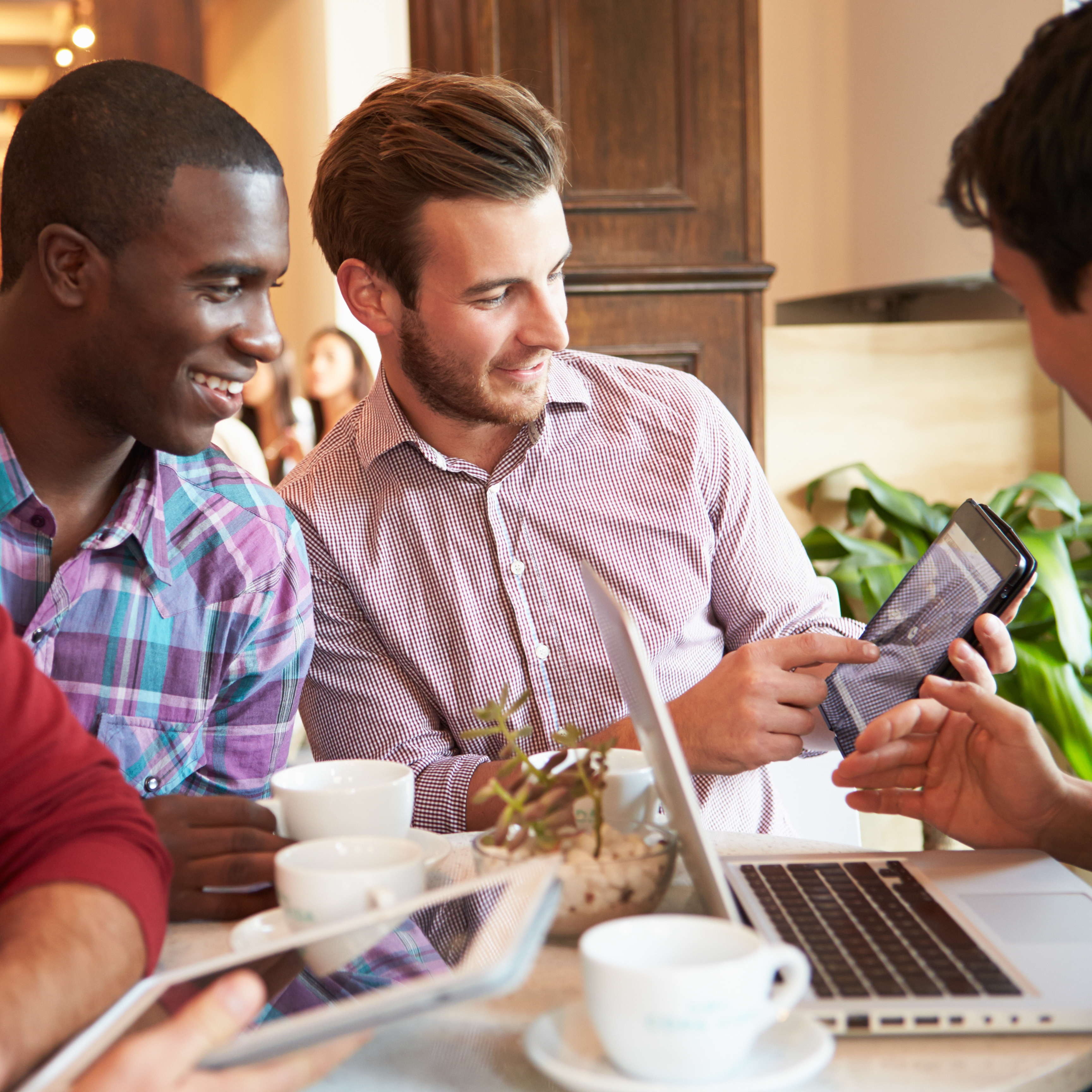 a group of young men laughing and enjoying each others company in a restaurant, looking at iPhones and iPads, computer information