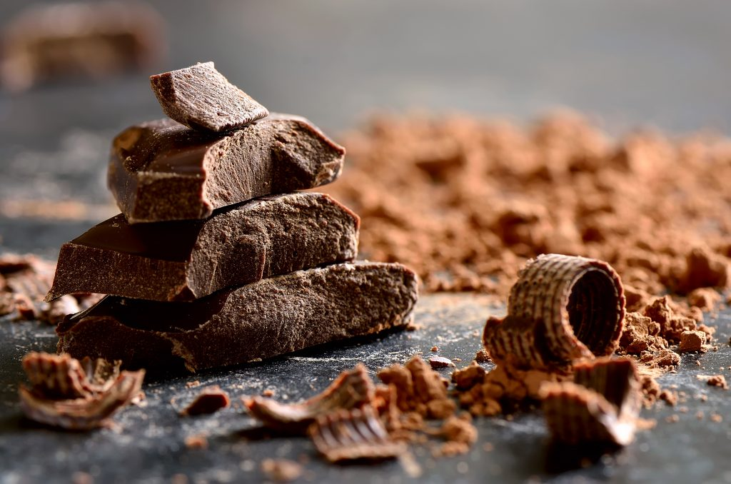a stack of dark chocolate with chips and powder