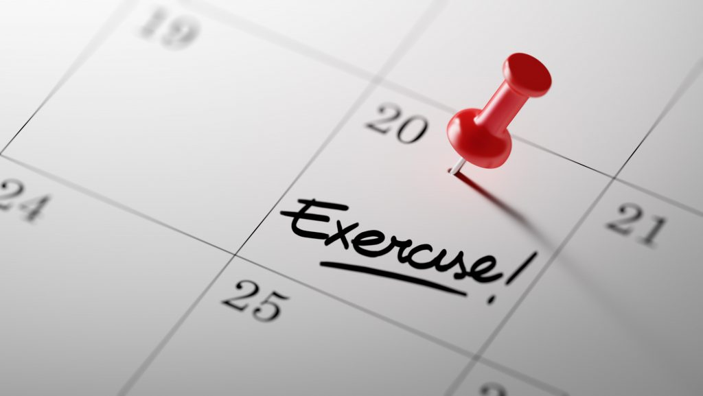 a close-up of a calendar, with a red push pin and the word Exercise! written on one date square and underlined