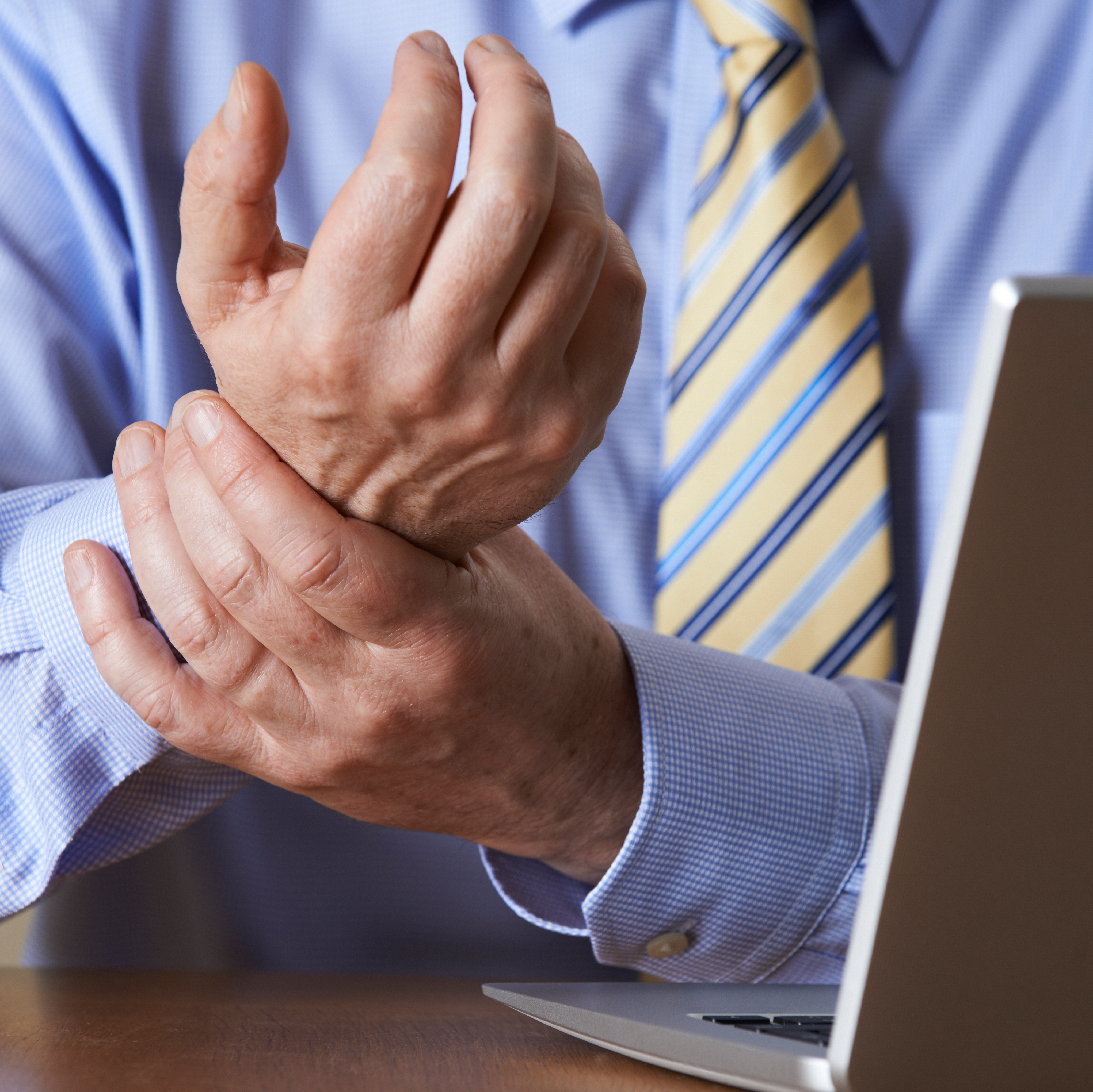 a business man sitting at a computer holding his wrist because of pain and injury