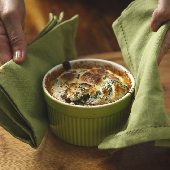 a person holding a dish with napkins - Spinach and mushroom soufflé