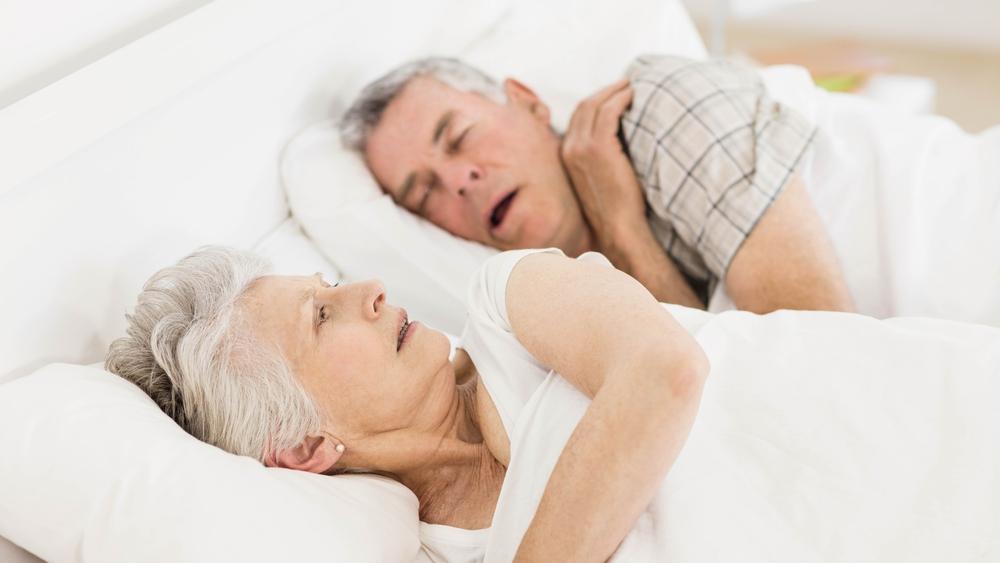 Una anciana está despierta en la cama mientras el marido ronca