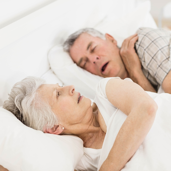 Awake senior woman in bed while her husband is snoring