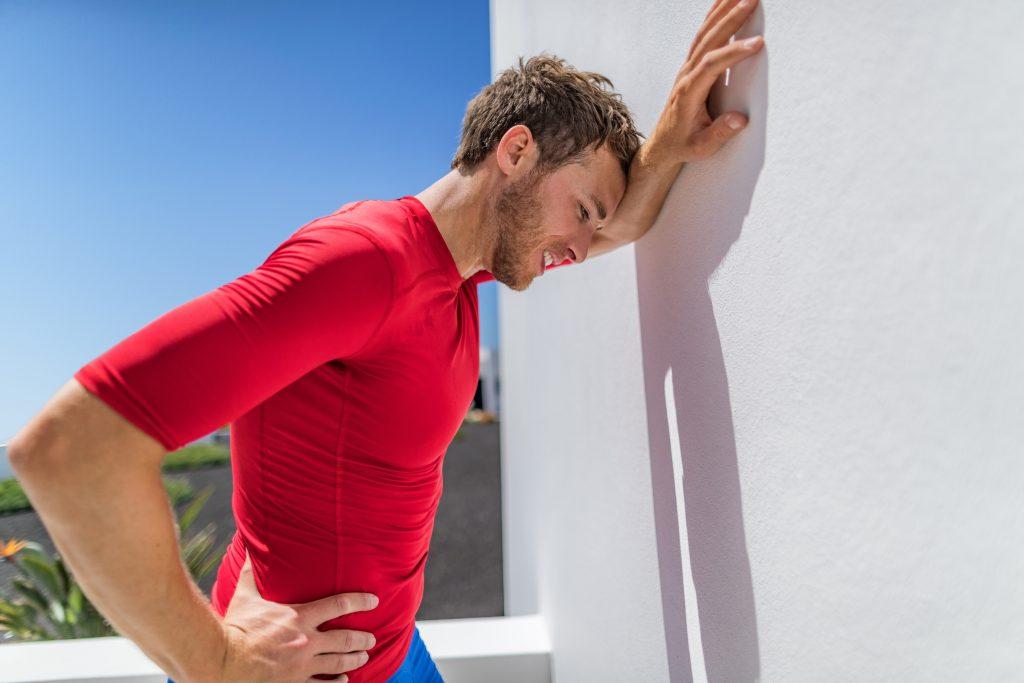 Un corredor exhausto se apoya contra una pared y respira con dificultad después del fuerte ejercicio, posiblemente debido a insolación, dolor de cabeza o agotamiento por calor