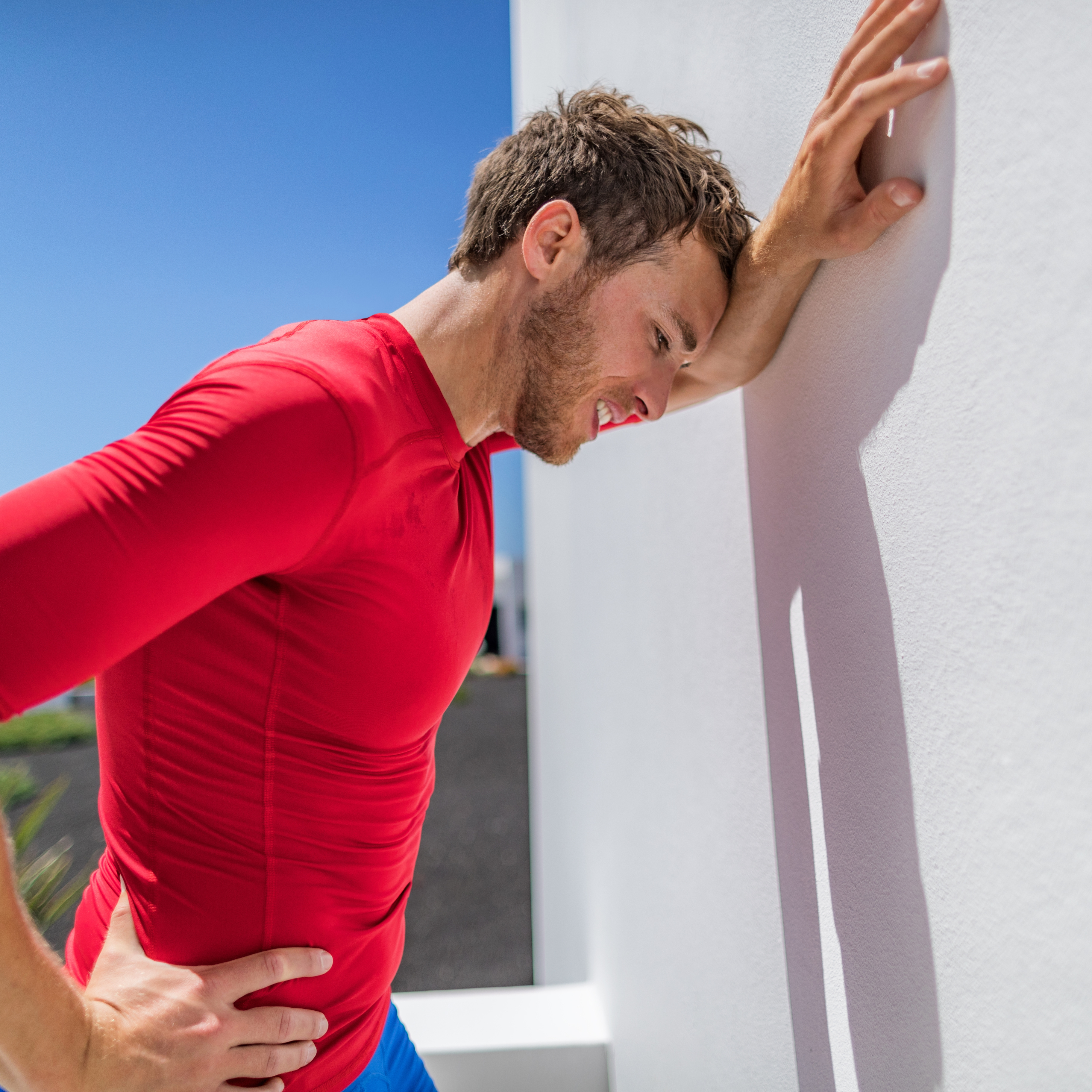 Exhausted male runner leaning on wall breathing hard after difficult exercise, perhaps with sun stroke, headache or heat exhaustion