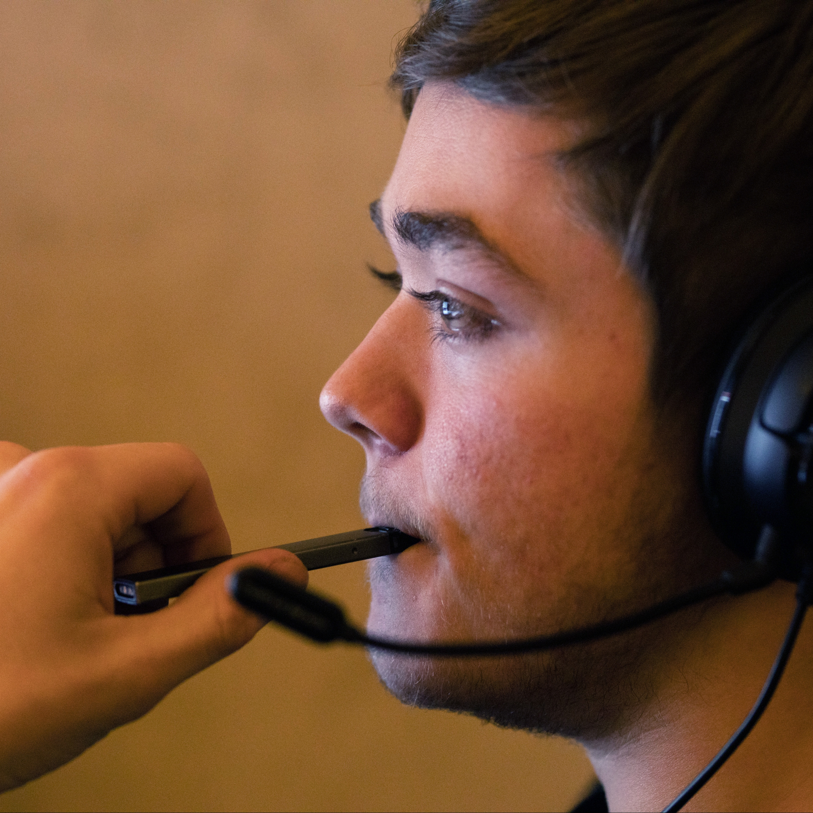 a young man vaping while playing a video game