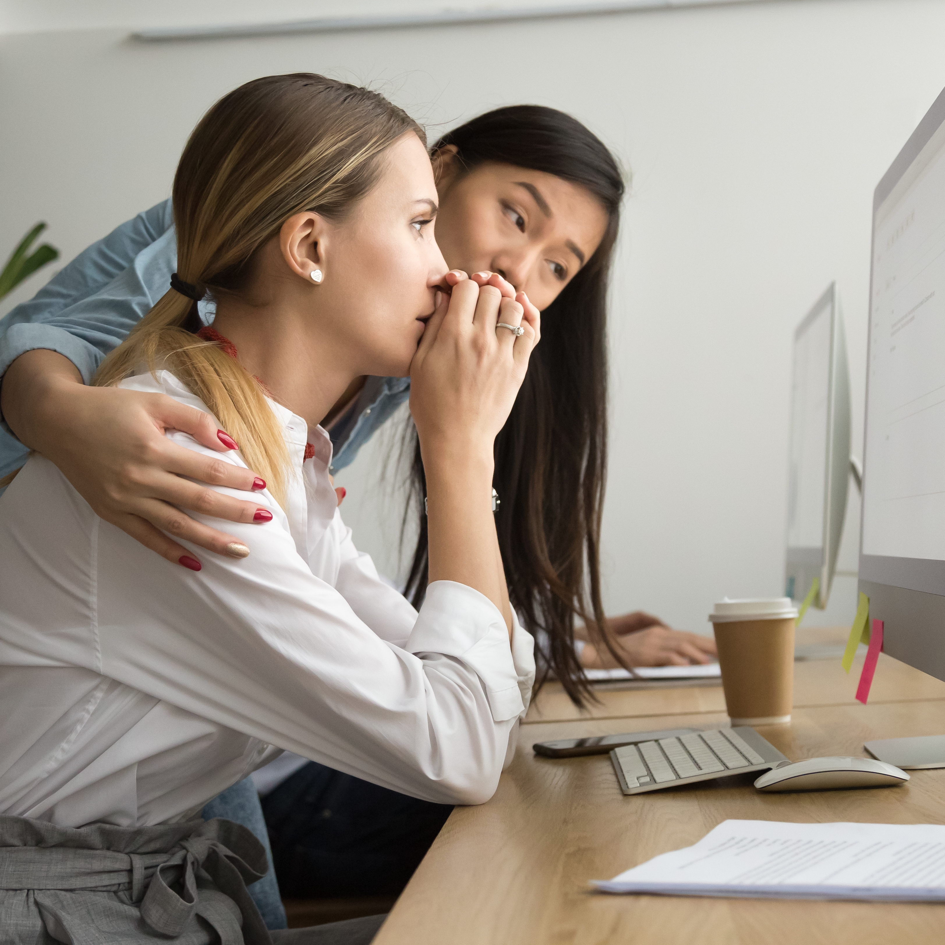 two young women in an office, one looking stressed and the other comforting her.