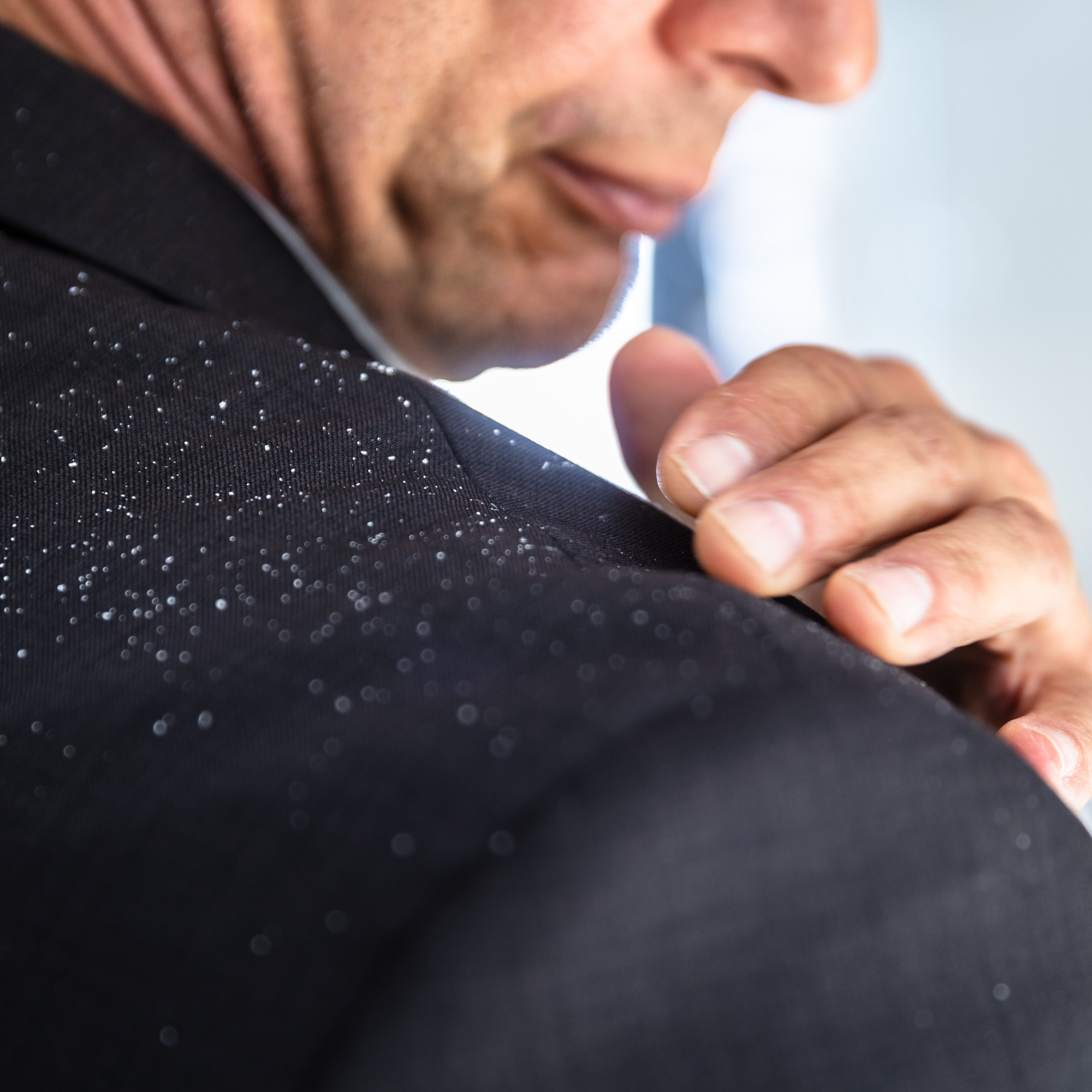 a man brushing dandruff flakes off his business jacket