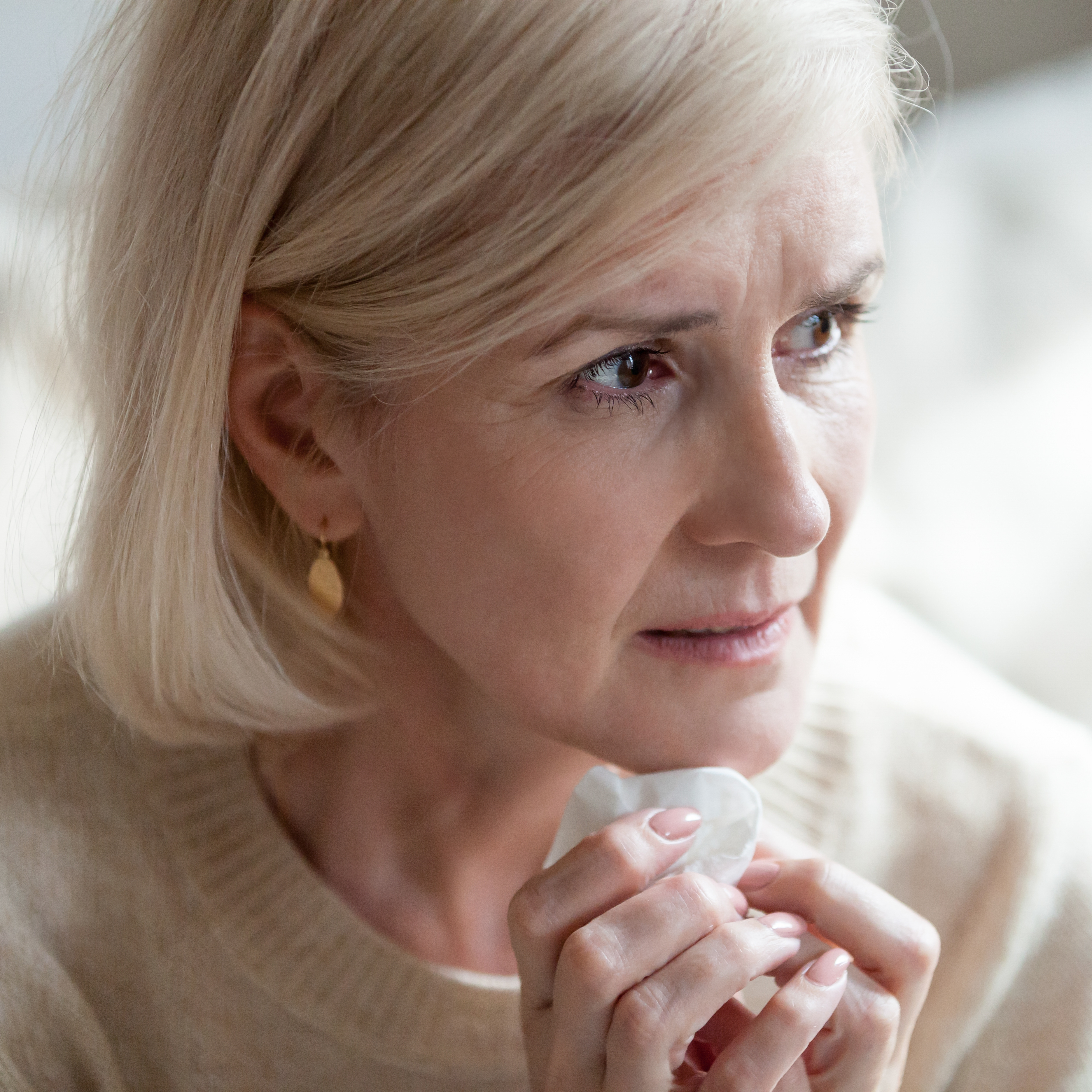 a middle aged woman holding a tissue looking worries, sad, concerned or frightened