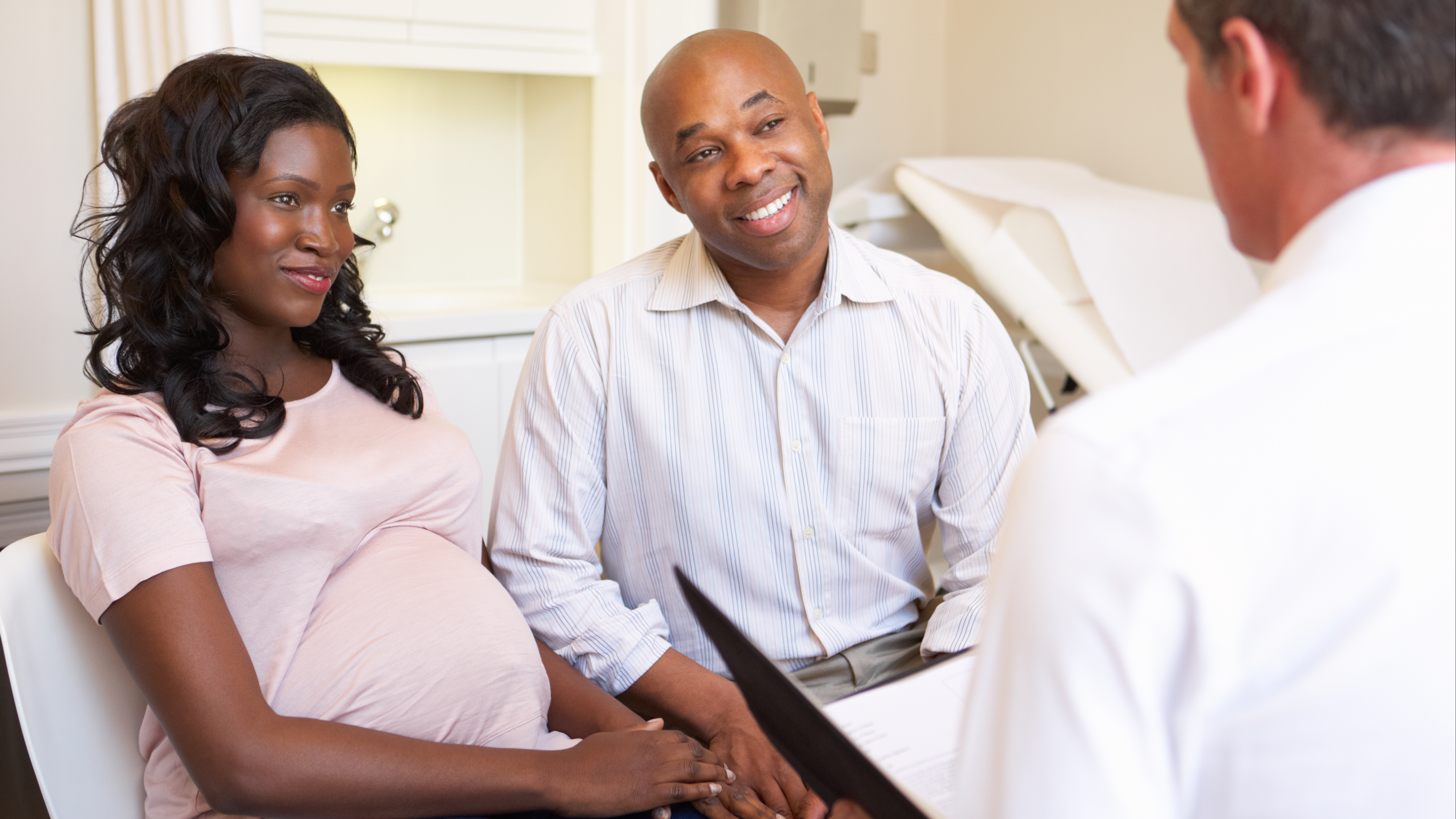 a young pregnant couple meeting with a physician, doctor for an appointment in an exam room