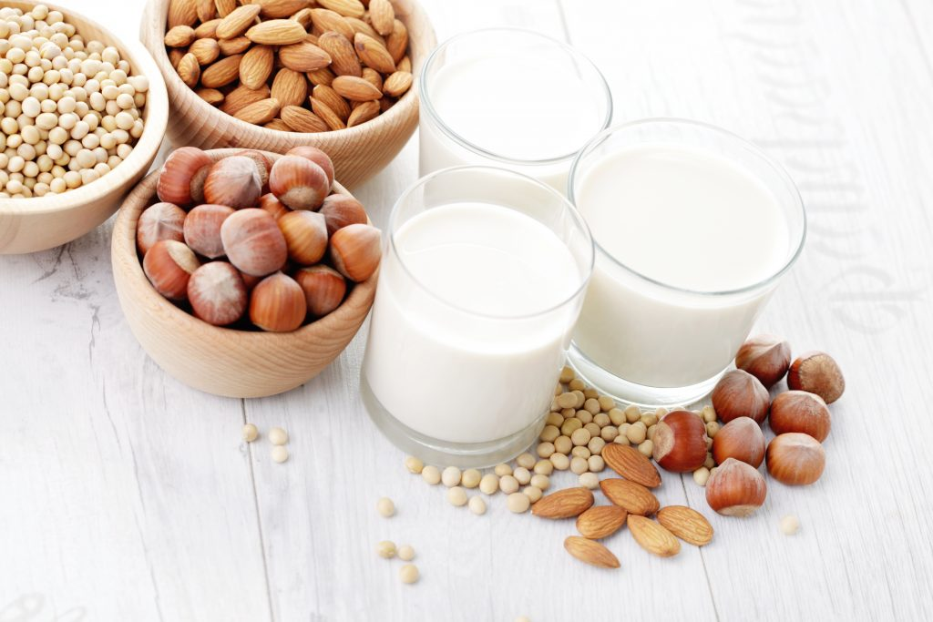 small wooden bowls filled with soybean, almonds and hazelnuts; and three glasses of the corresponding plant milks