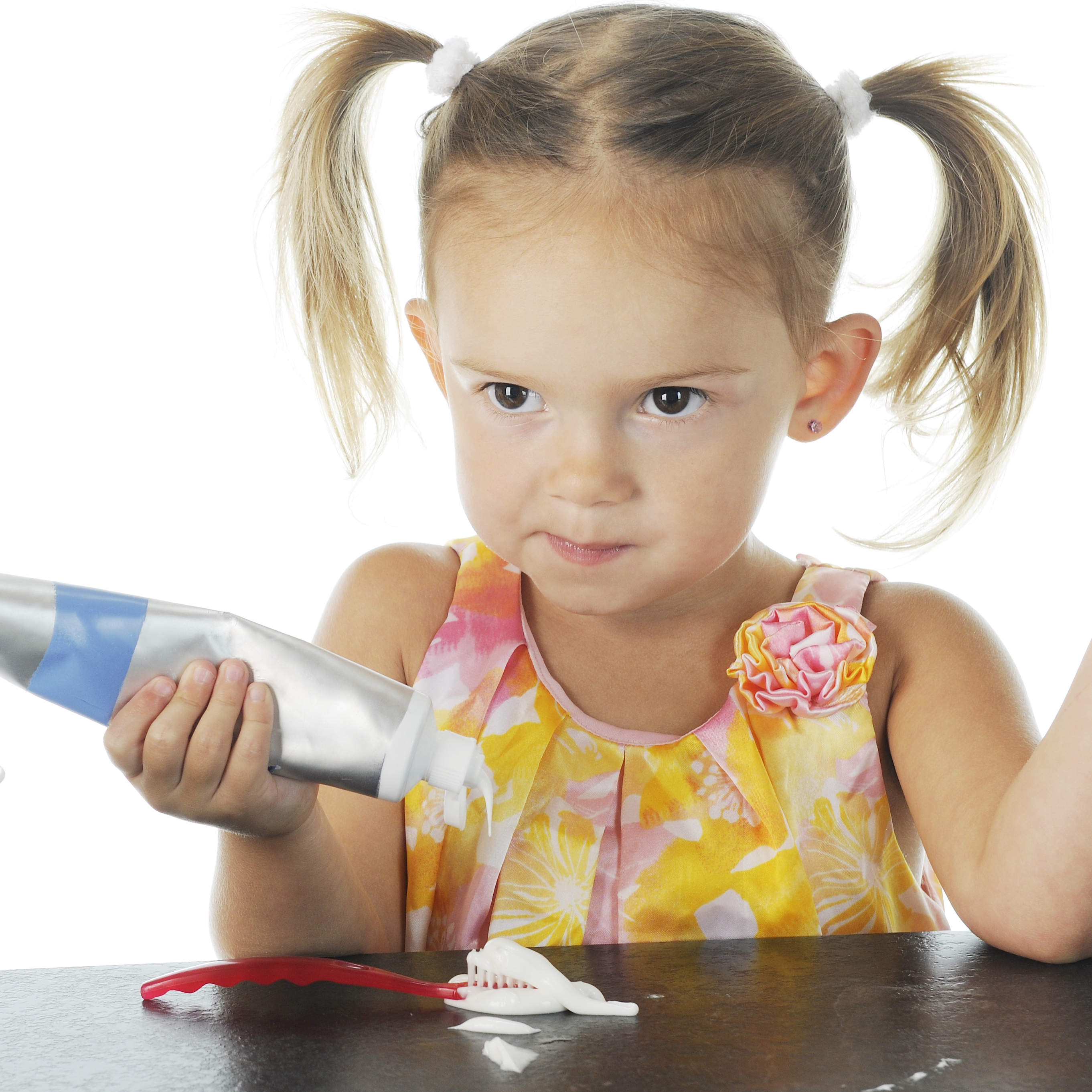 a little girl with a determined look on her face while squeezing a lot of toothpaste on a toothbrush