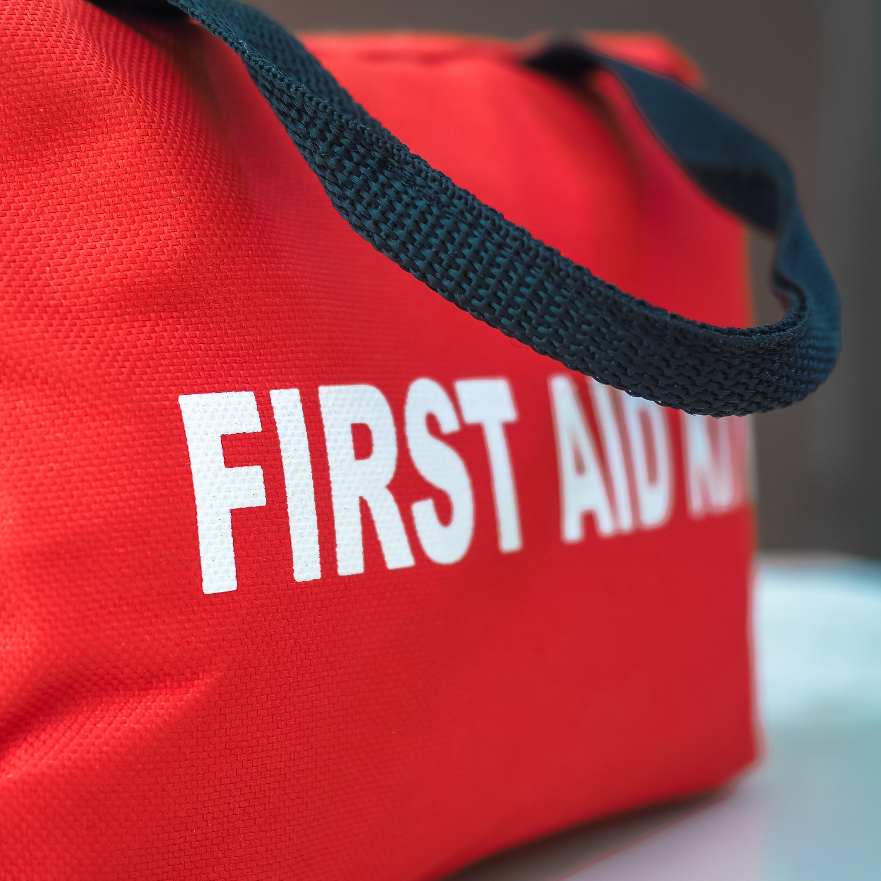 a red canvas bag with the words First Aid Kit