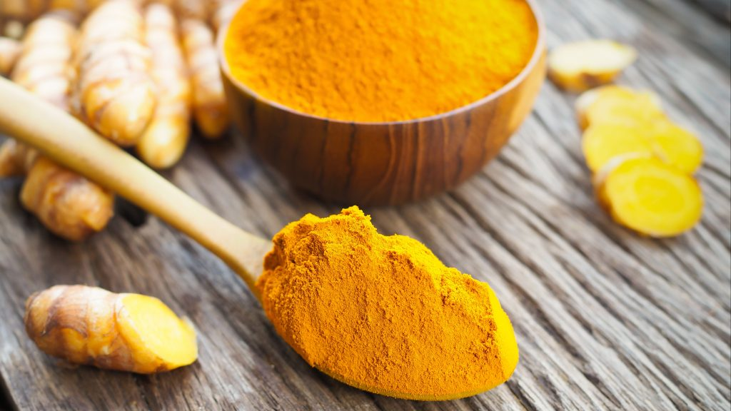 Turmeric powder in wooden spoon on old wooden table.