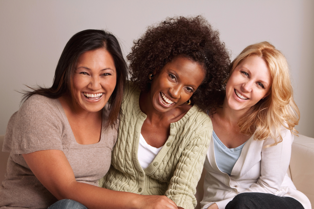 three young women laughing and smiling together