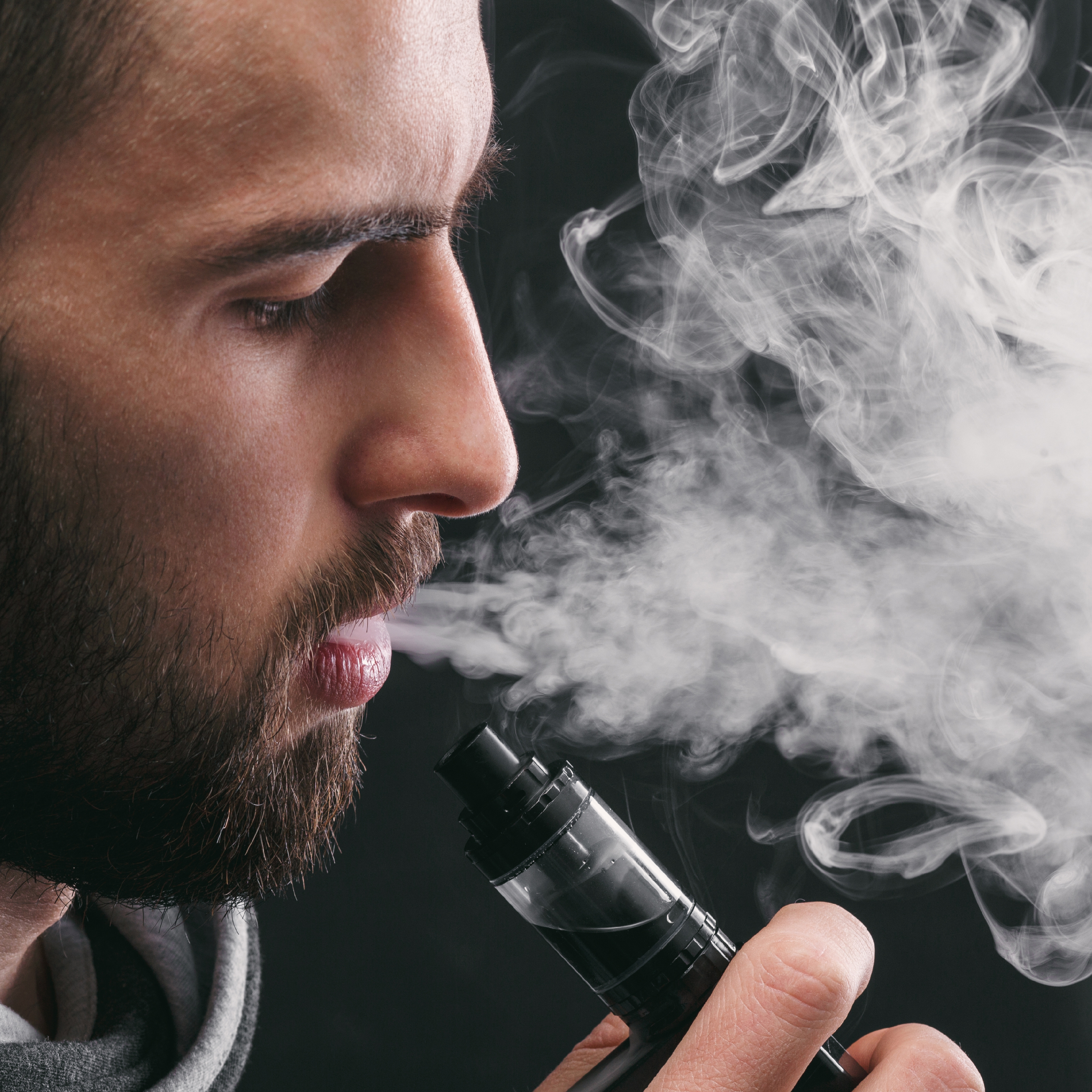 a young man exhaling from a vaping tool