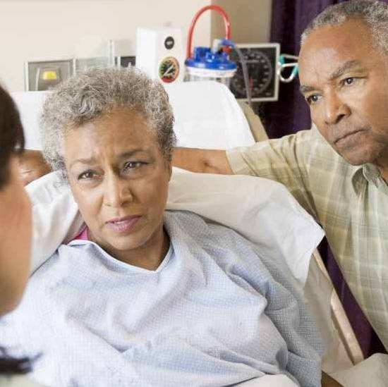 African American woman in a hospital bed, perhaps with her husband, listening to the doctor