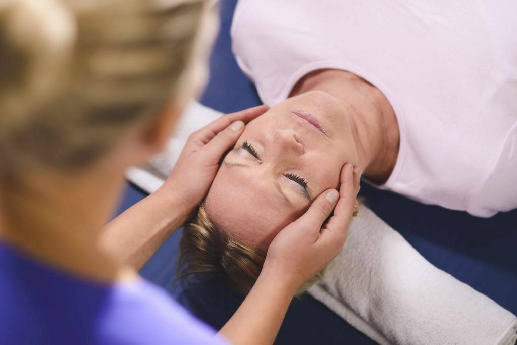 young woman doing reiki massage treatment on another woman