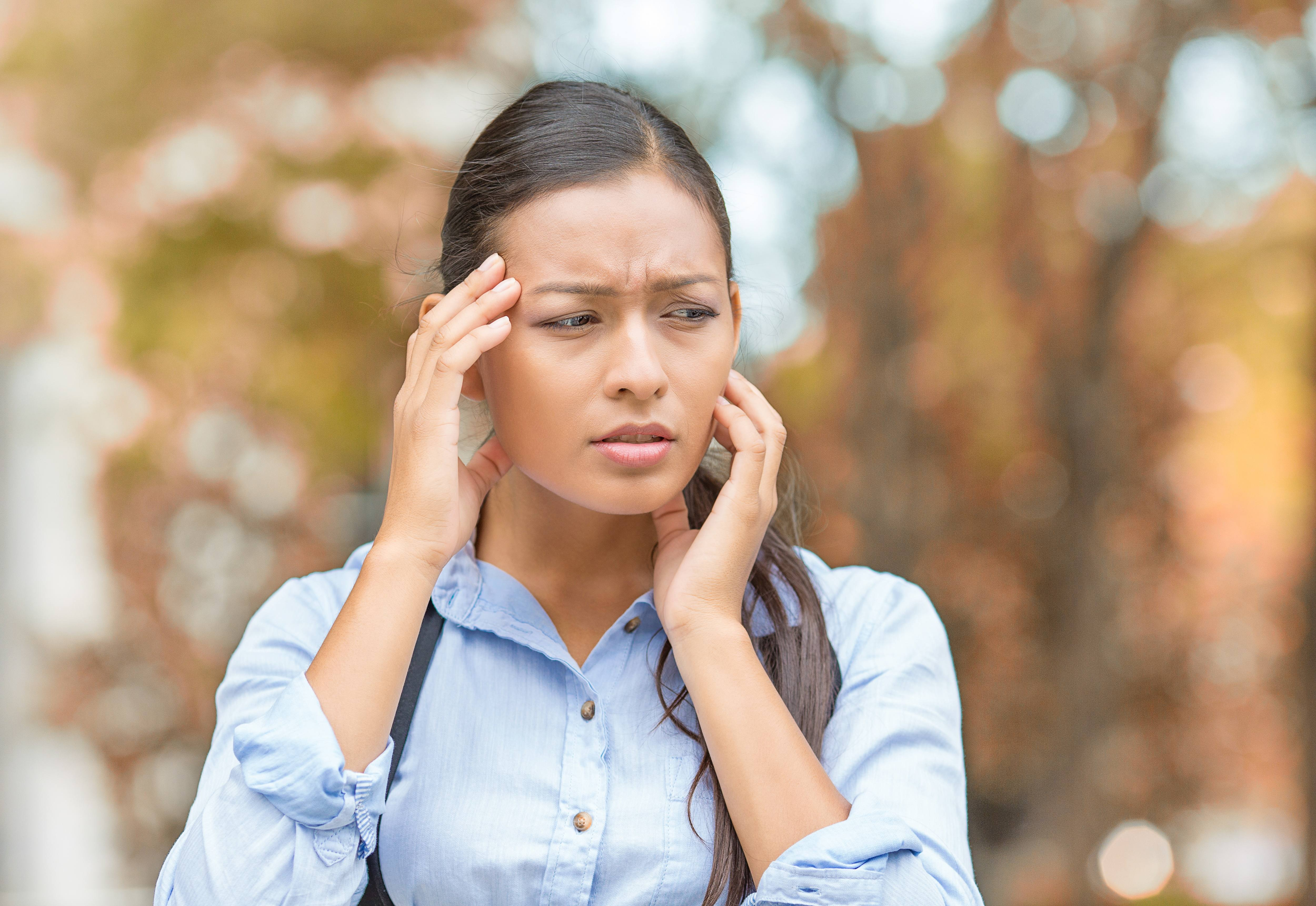 Close-up portrait of woman with hands on head having headache outside with a background of autumn trees