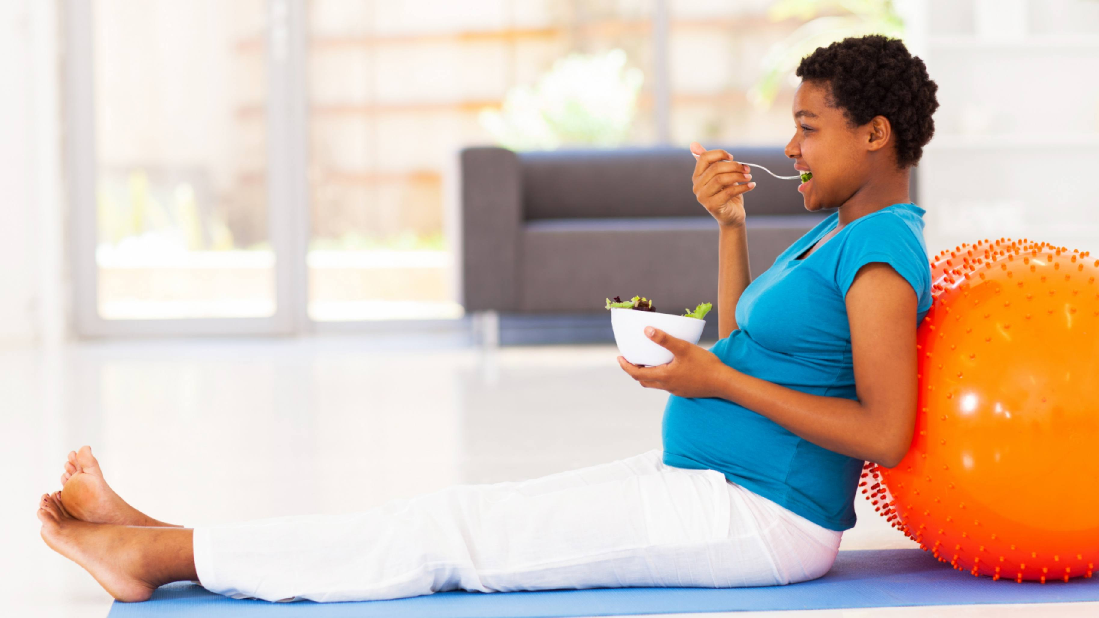 a young African American pregnant woman sitting on a floor with an exercise ball and eating a healthy salad