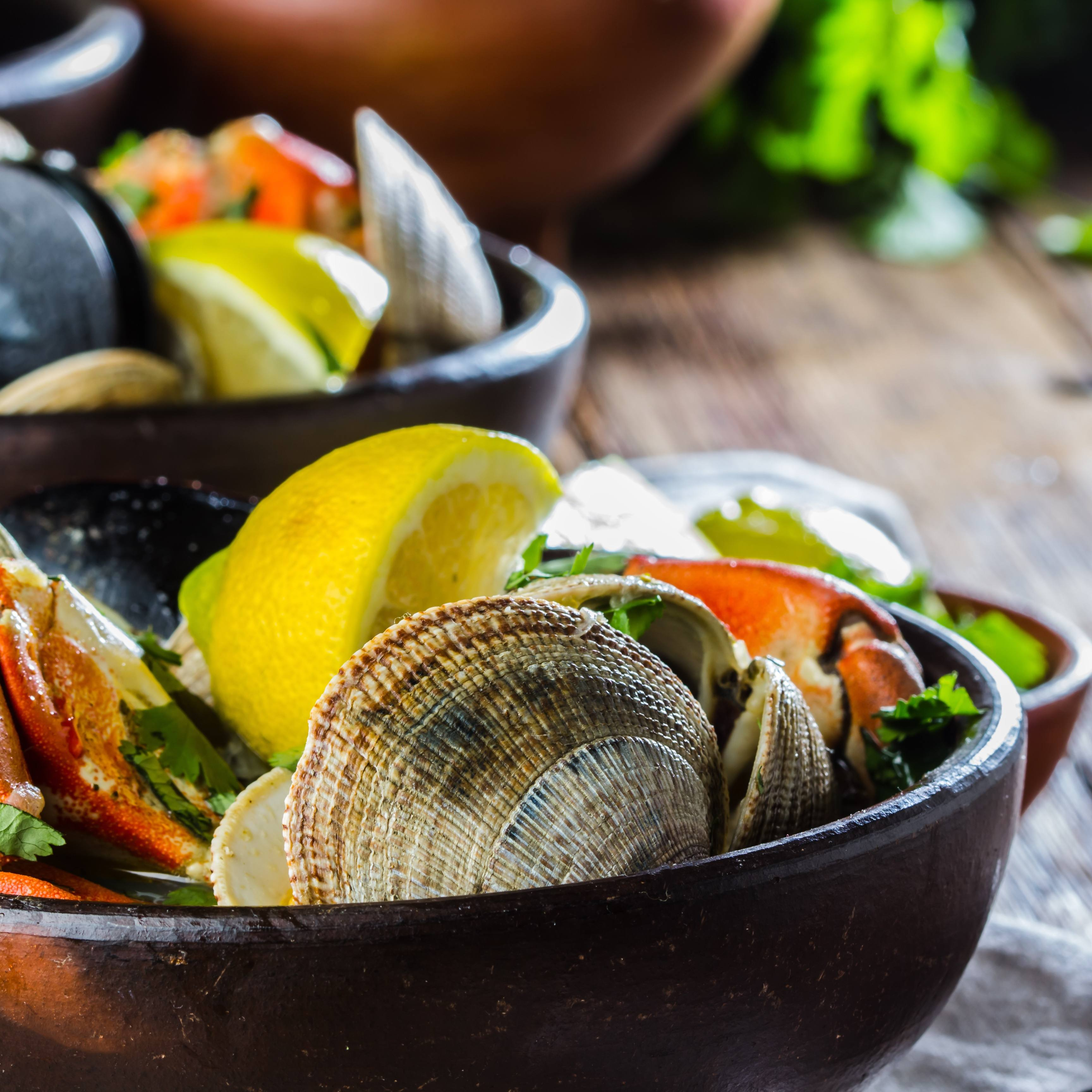 Seafood shellfish soup of mussels, crabs, clams and other shellfish served in clay bowls.