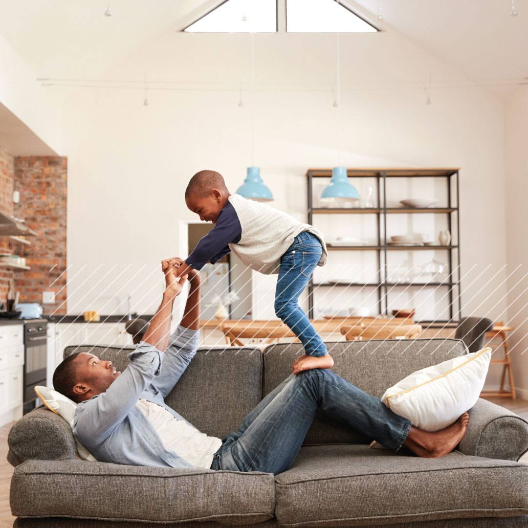 man playing with son on sofa