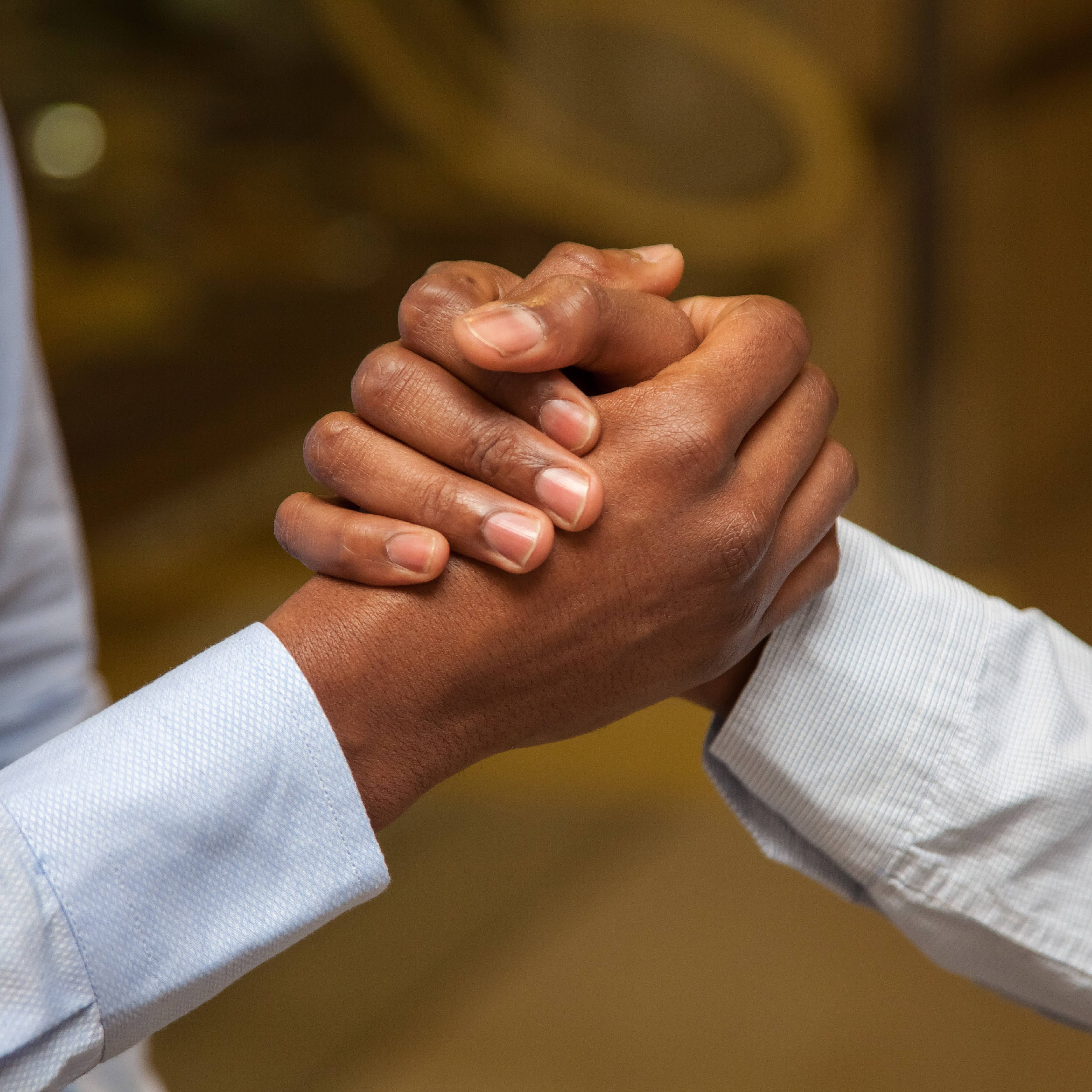 a close-up of two men's hands clasped