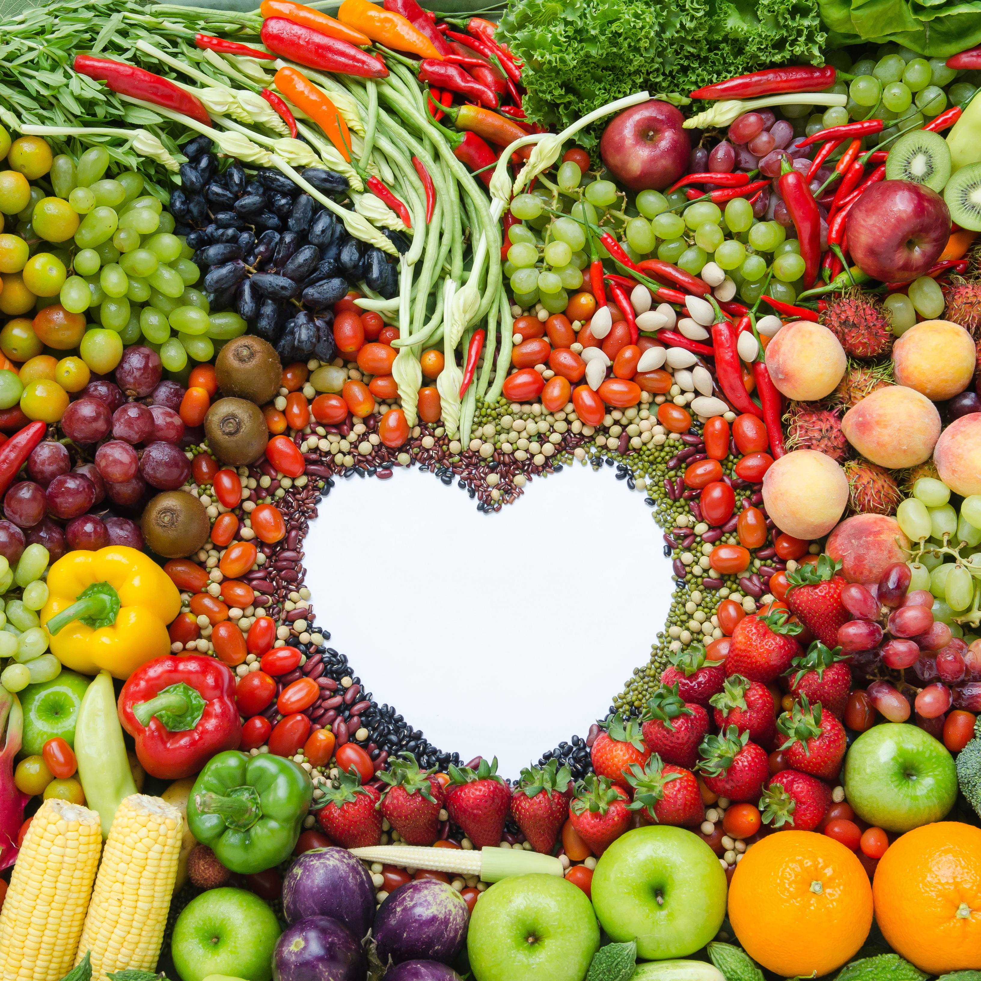 assorted fruits, vegetables and legumes arranged around a blank heart shape