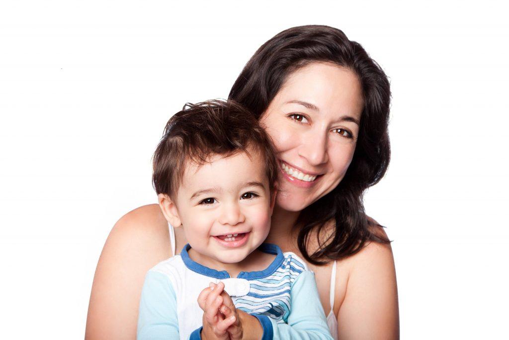 Una madre sostiene a su hijo y ambos sonríen