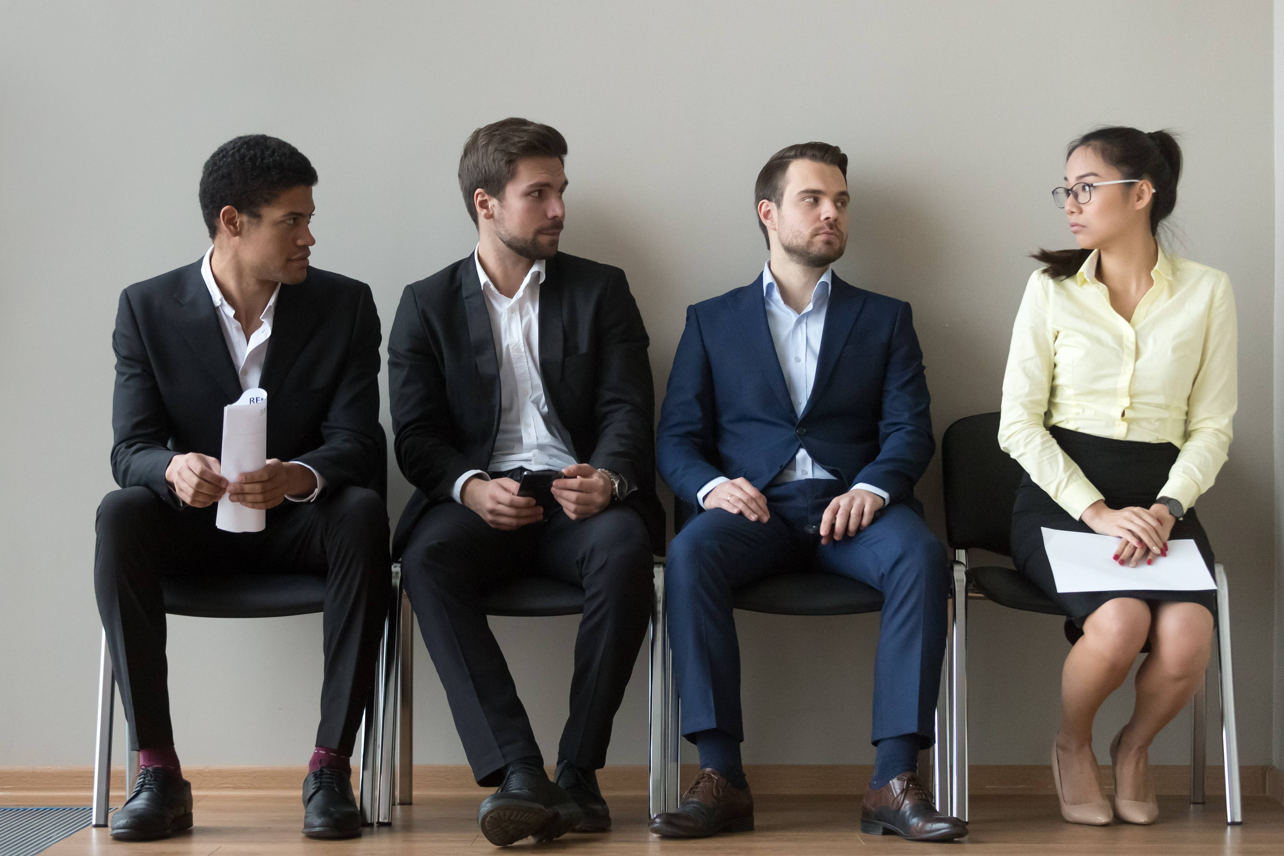 three males and one female seated in a row, unfair gender discrimination at work concept