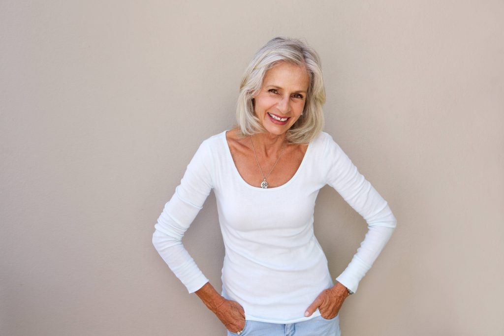 a thin, smiling older woman with her hands in her pants pockets, standing in front of a blank wall