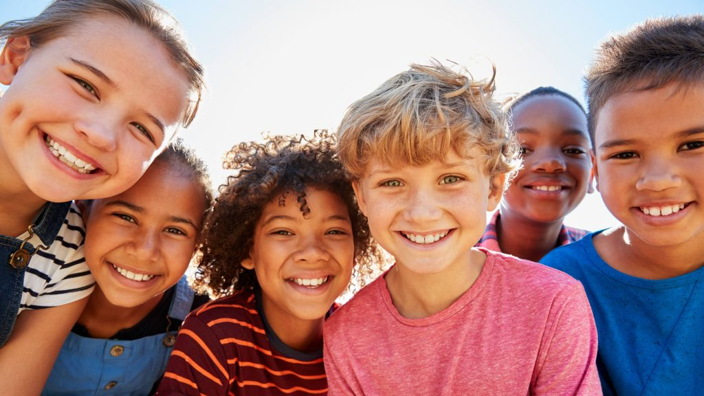 a group of happy children laughing and smiling outside in the sunshine