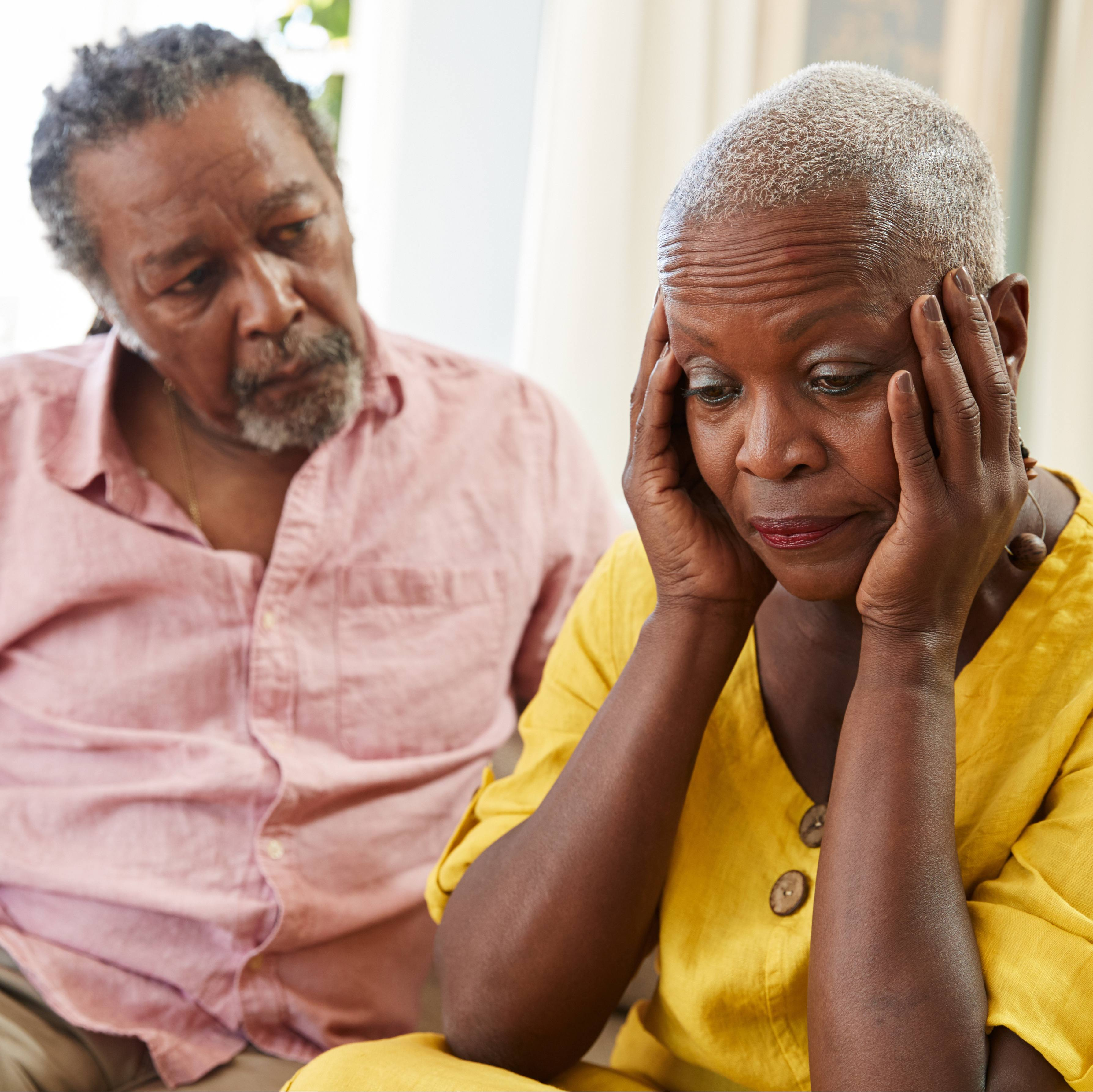 a sad and worried looking African American middle-aged couple sitting on a couch, with the woman holding her head