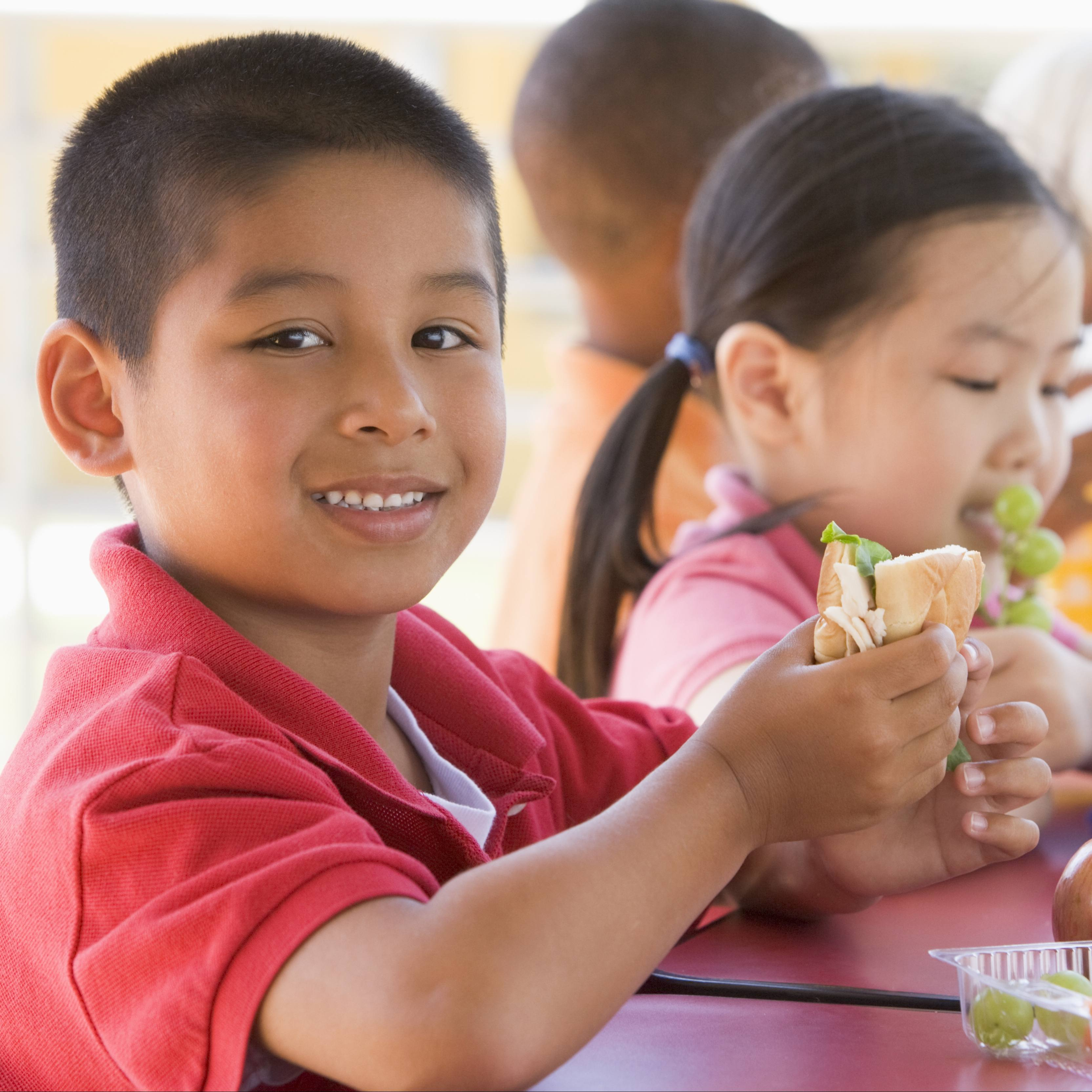 children eating at a school lunch table, a little boy holding a sandwich and a little girl eating grapes