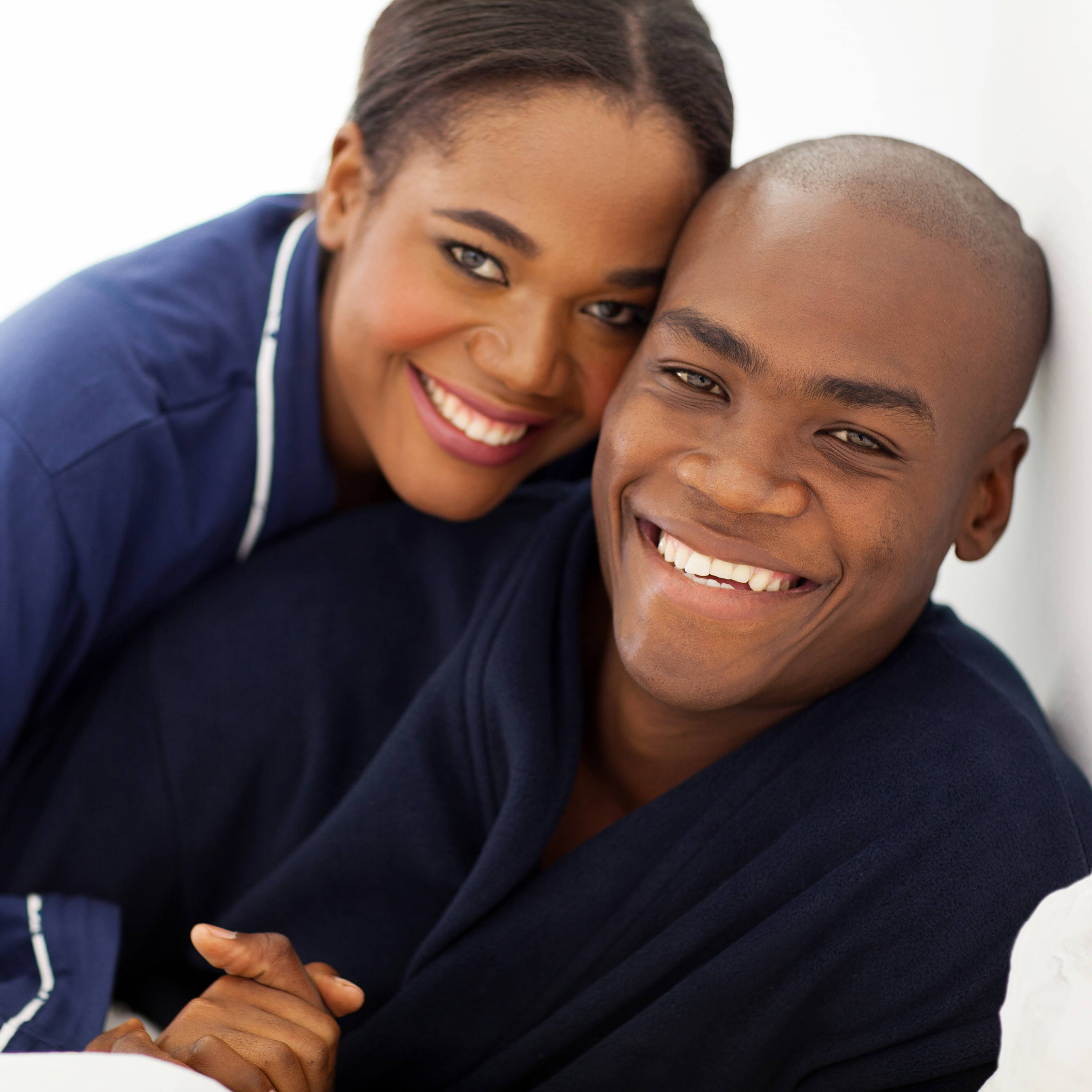 a happy, smiling young couple in pajamas