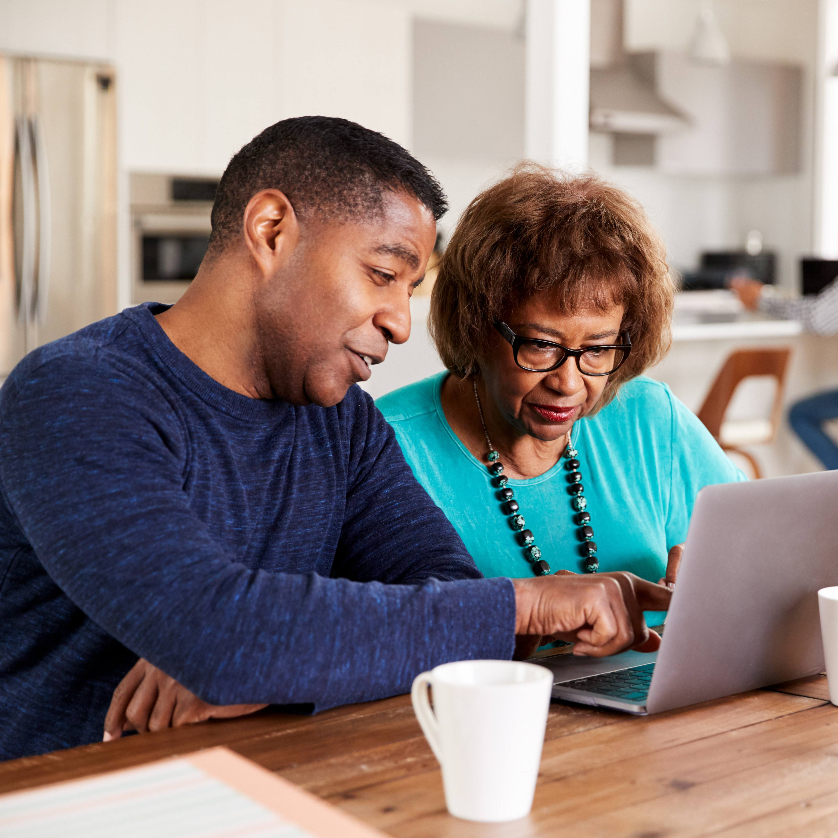 a middled-aged man helping an older woman with something on the screen of a laptop