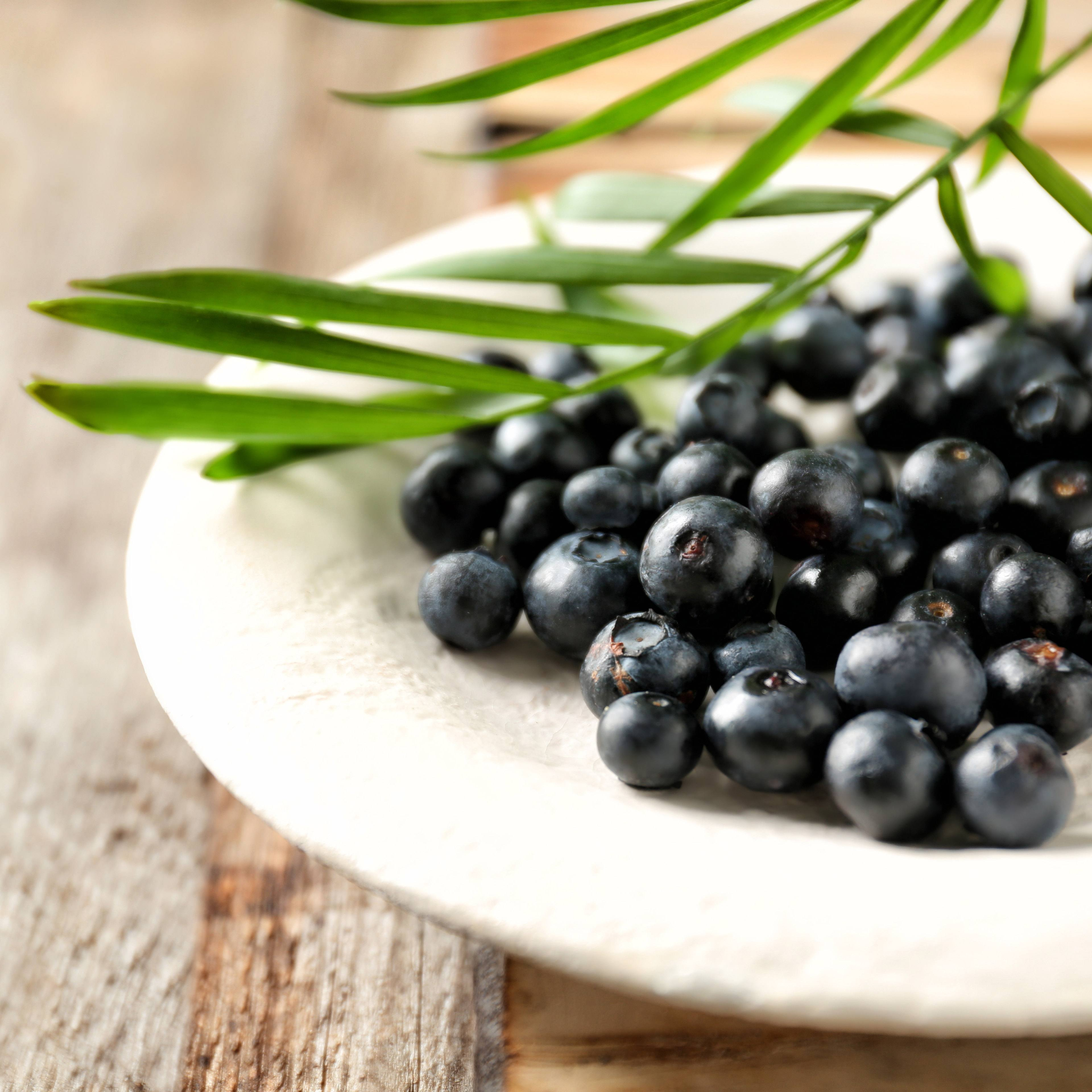 a plate of fresh acai berries on a rough wooden table