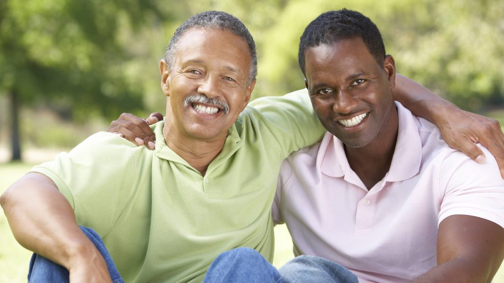 a smiling middle-aged father and his adult son, sitting outside, each with an arm around the shoulders of the other