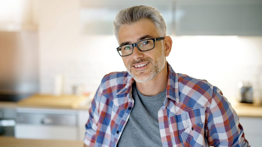 a smiling middle-aged man with glasses and a grey beard and hair