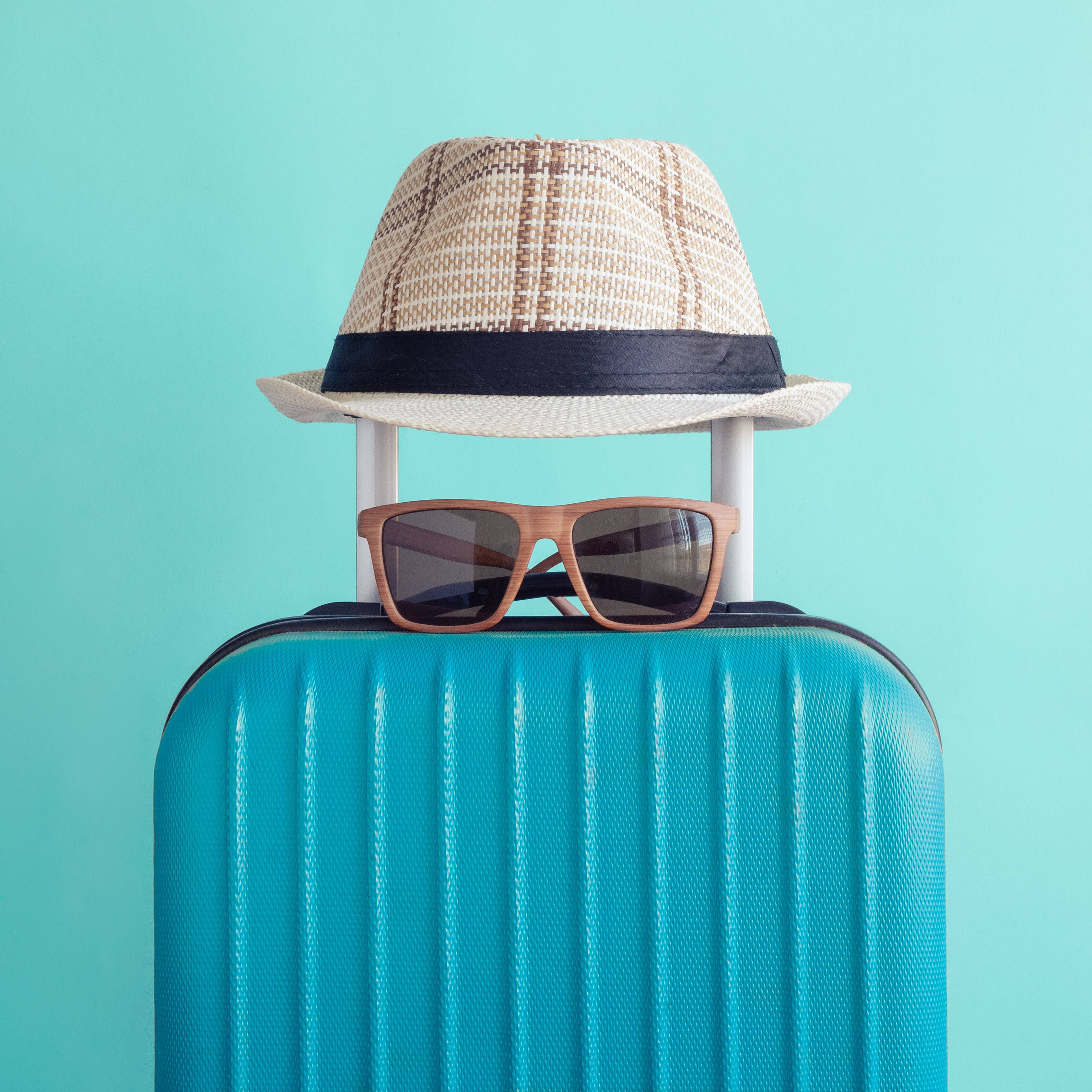 a suitcase with a hat and pair of sunglasses