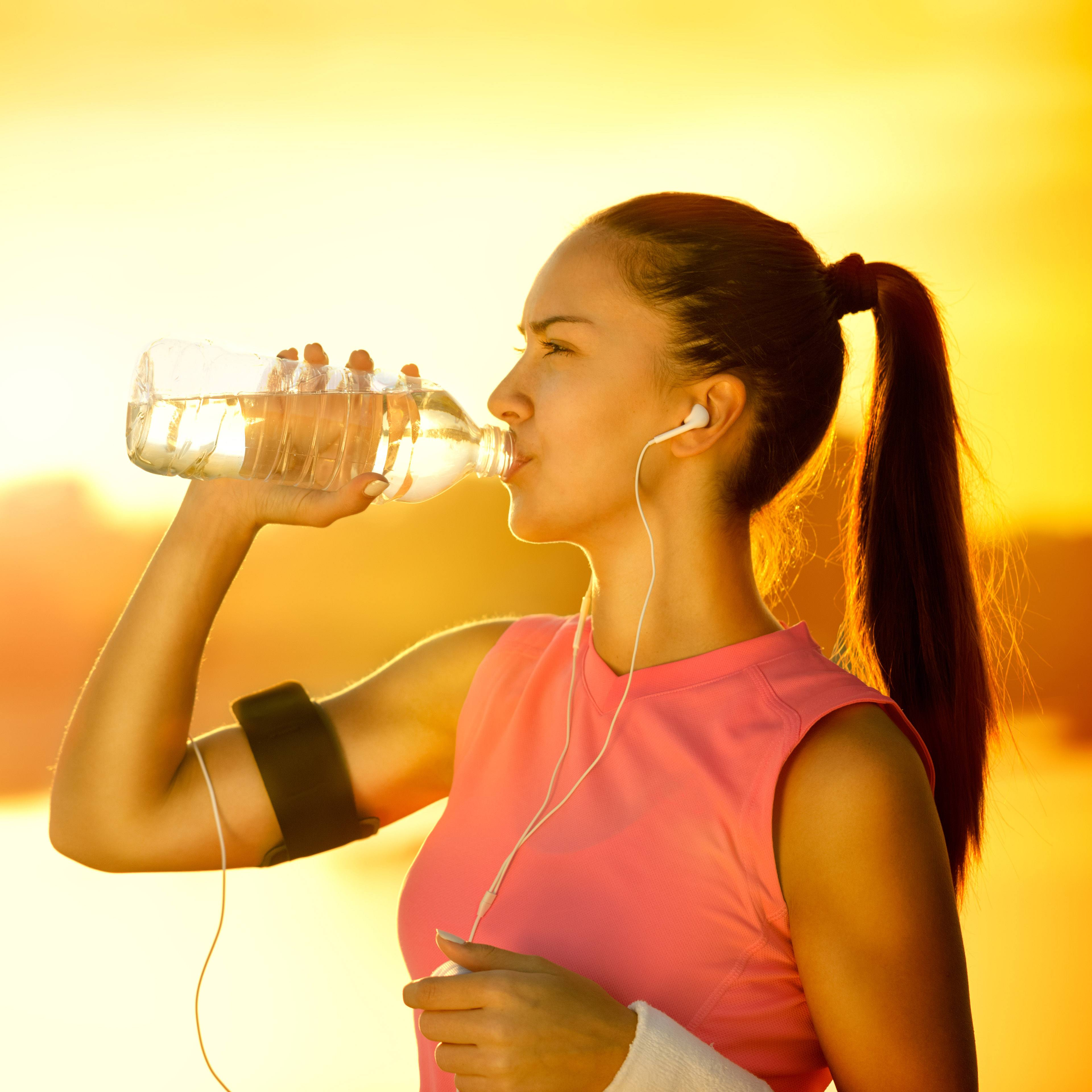 a young woman outdoors on a sunny day, drinking water and dressed for running
