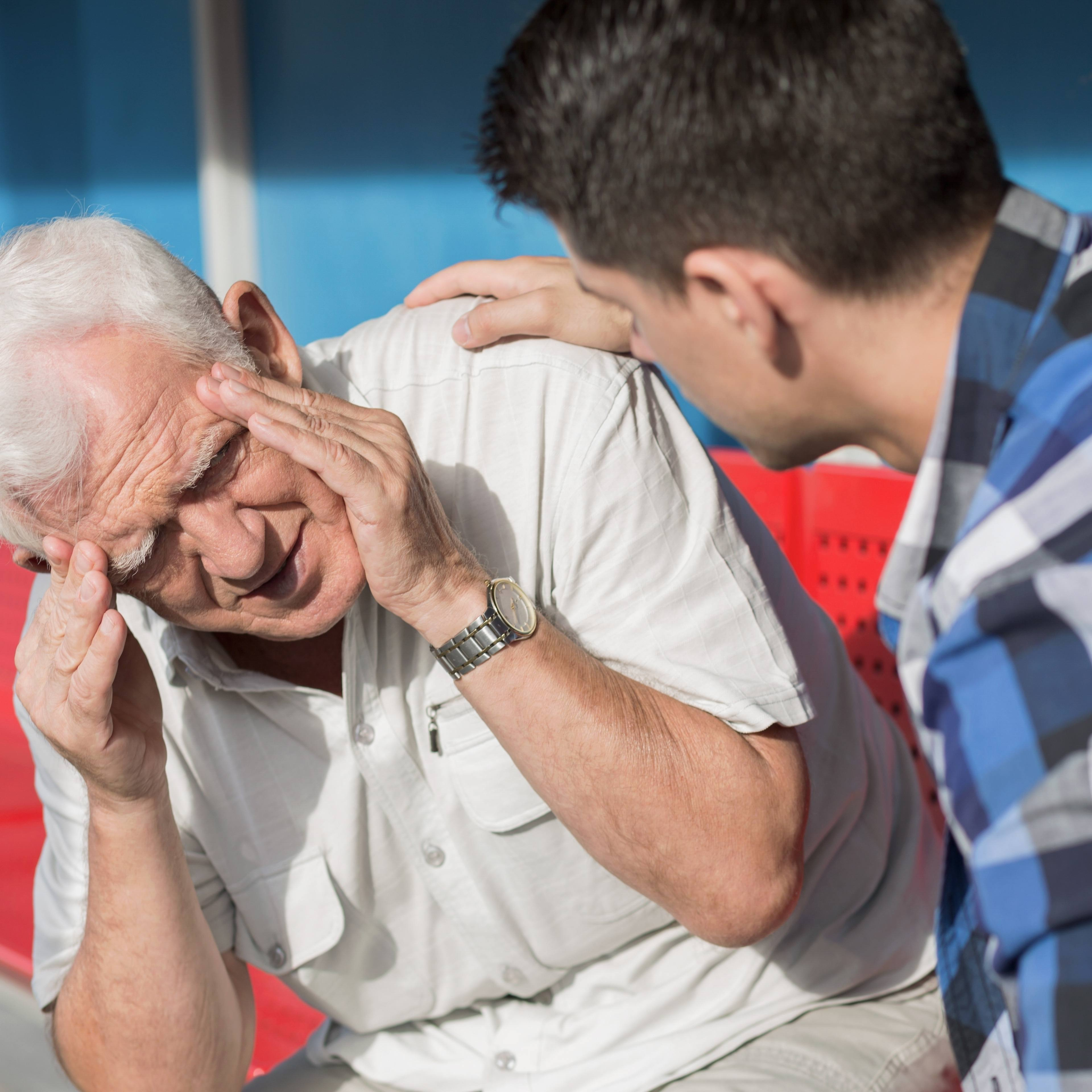 Senior man suffering from dizziness with concerned younger man