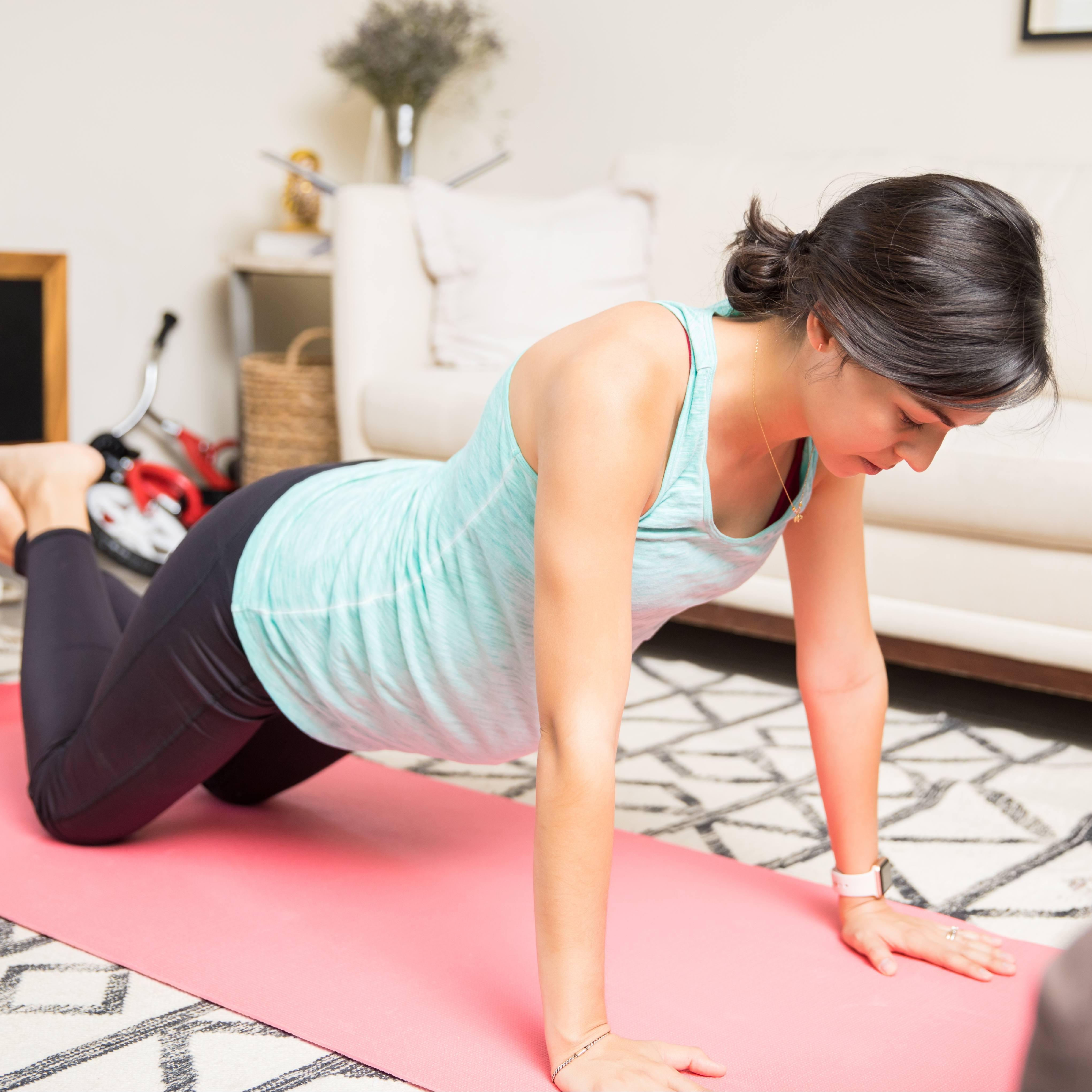 a pregnant Caucasian woman exercising on a yoga mat