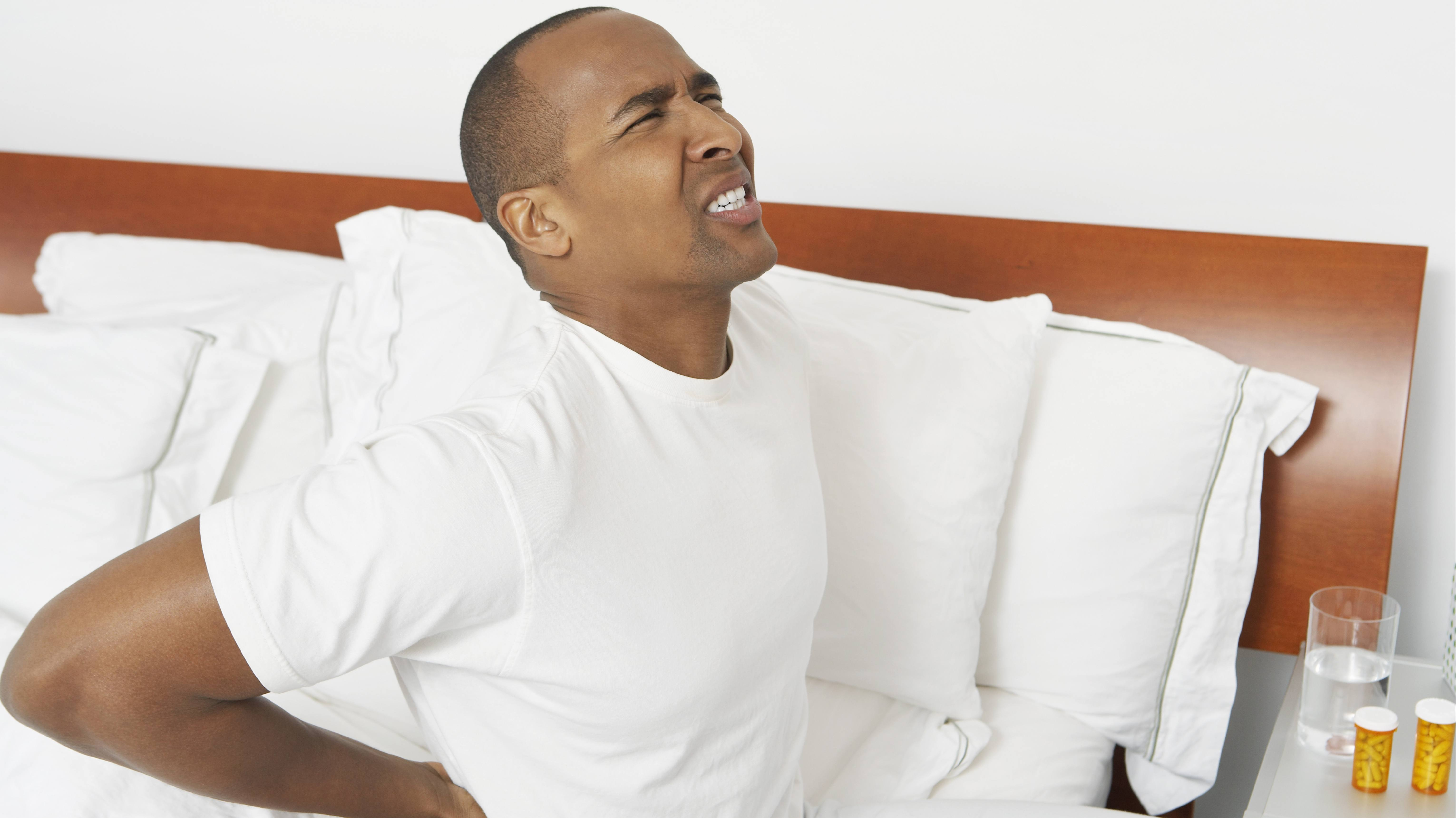 a young African American man sitting on the edge of a bed suffering with back pain