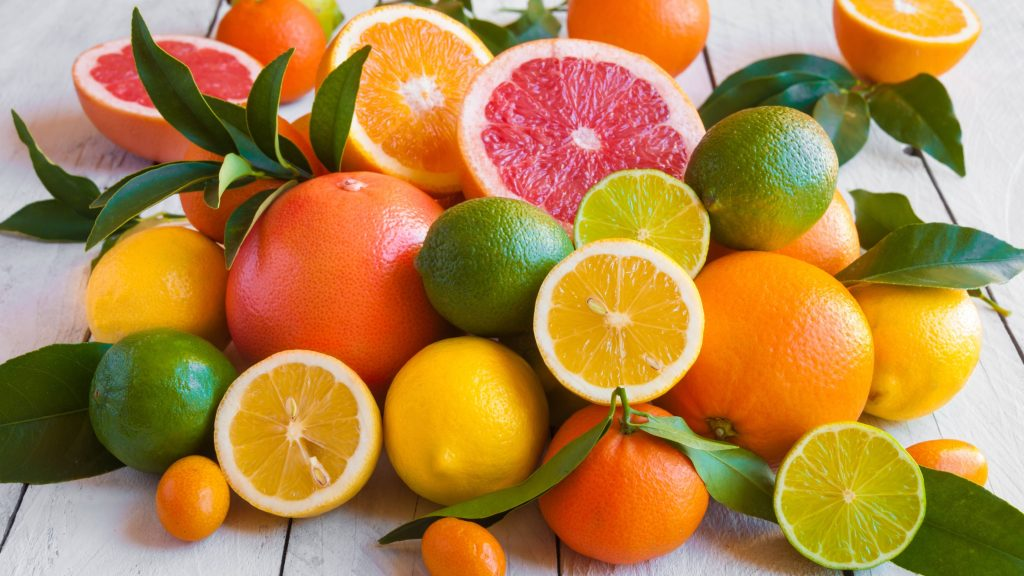 a collection of fruit on a wooden counter, with oranges, lemons, limes and grapefruits