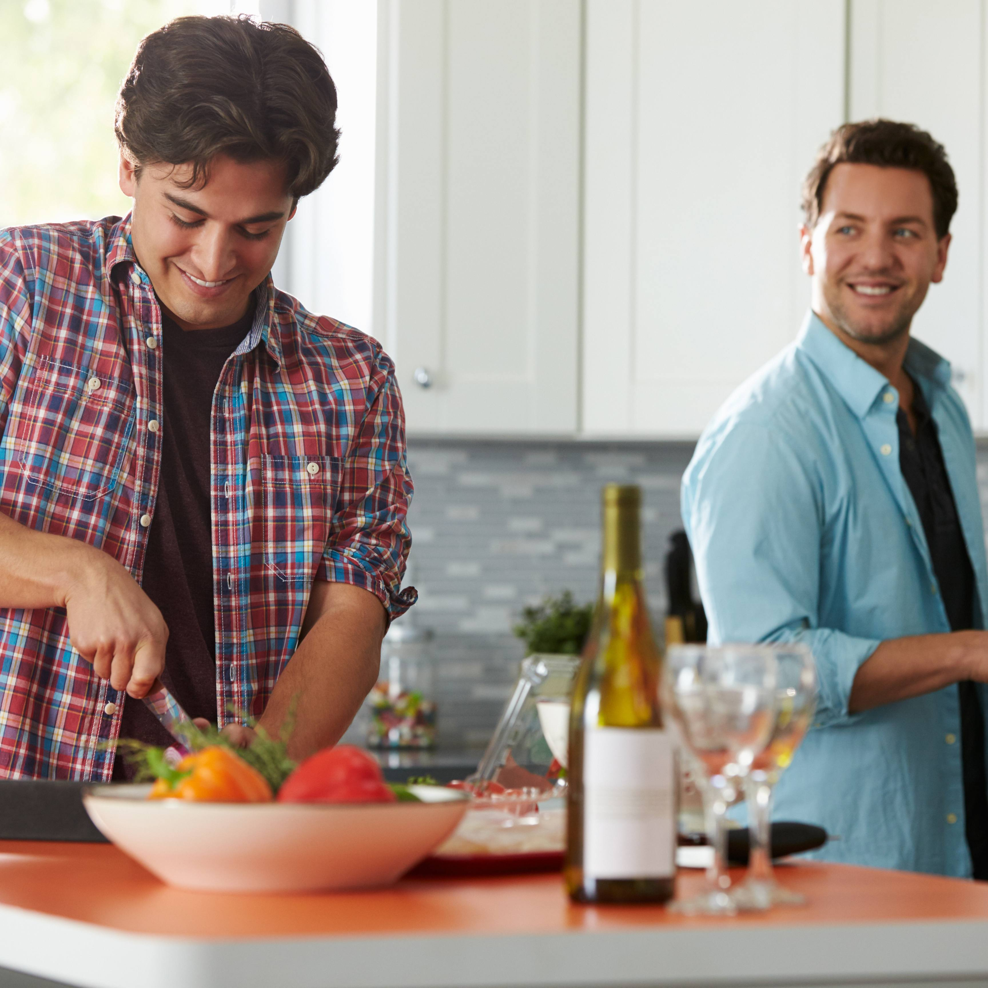 two young men cooking together in their kitchen