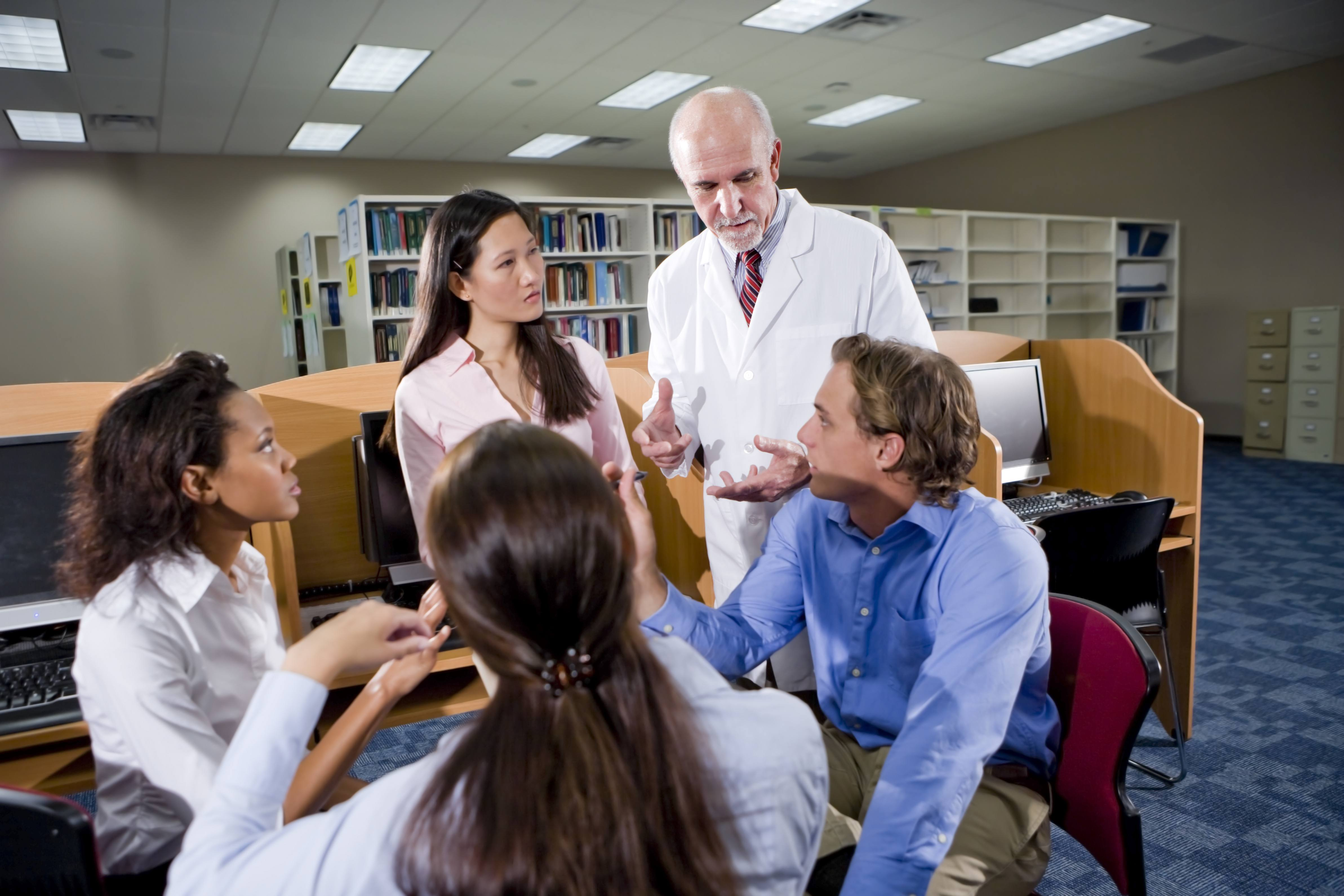 Multiracial students with professor conversing in library