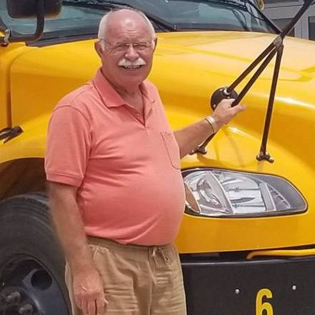 Sharing Mayo Clinic patient Mike Ramsey smiling and standing beside a school bus.