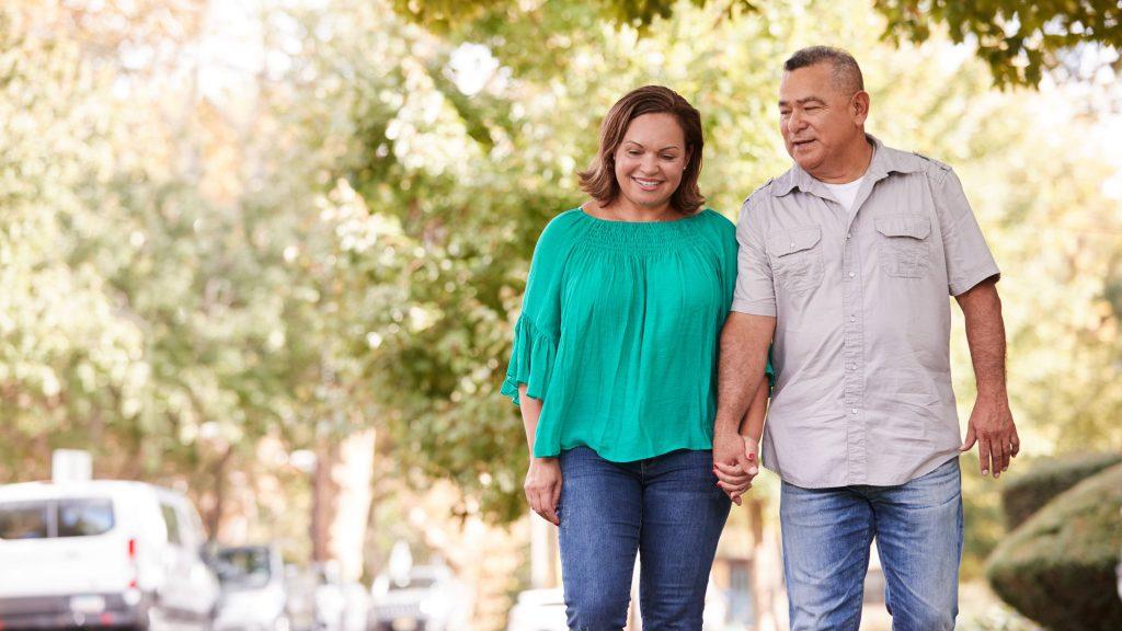 Las parejas ancianas caminando por la calle suburbana tomados de la mano