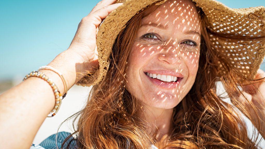 Una sonriente mujer de mediana edad lleva puesto un sombrero de paja en un día soleado